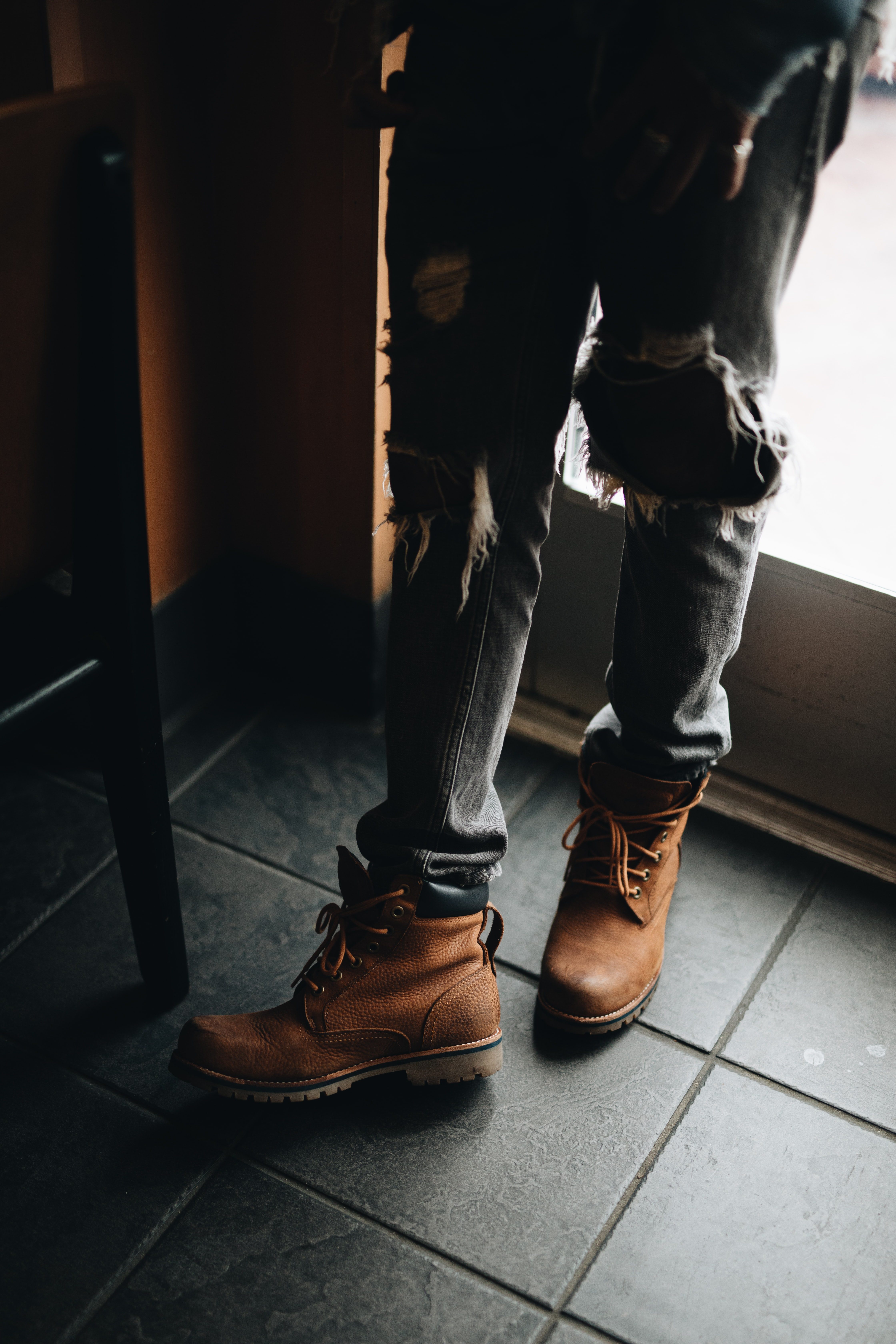 person wearing distressed blue denim jeans and pair of brown leather work boots beside glass door