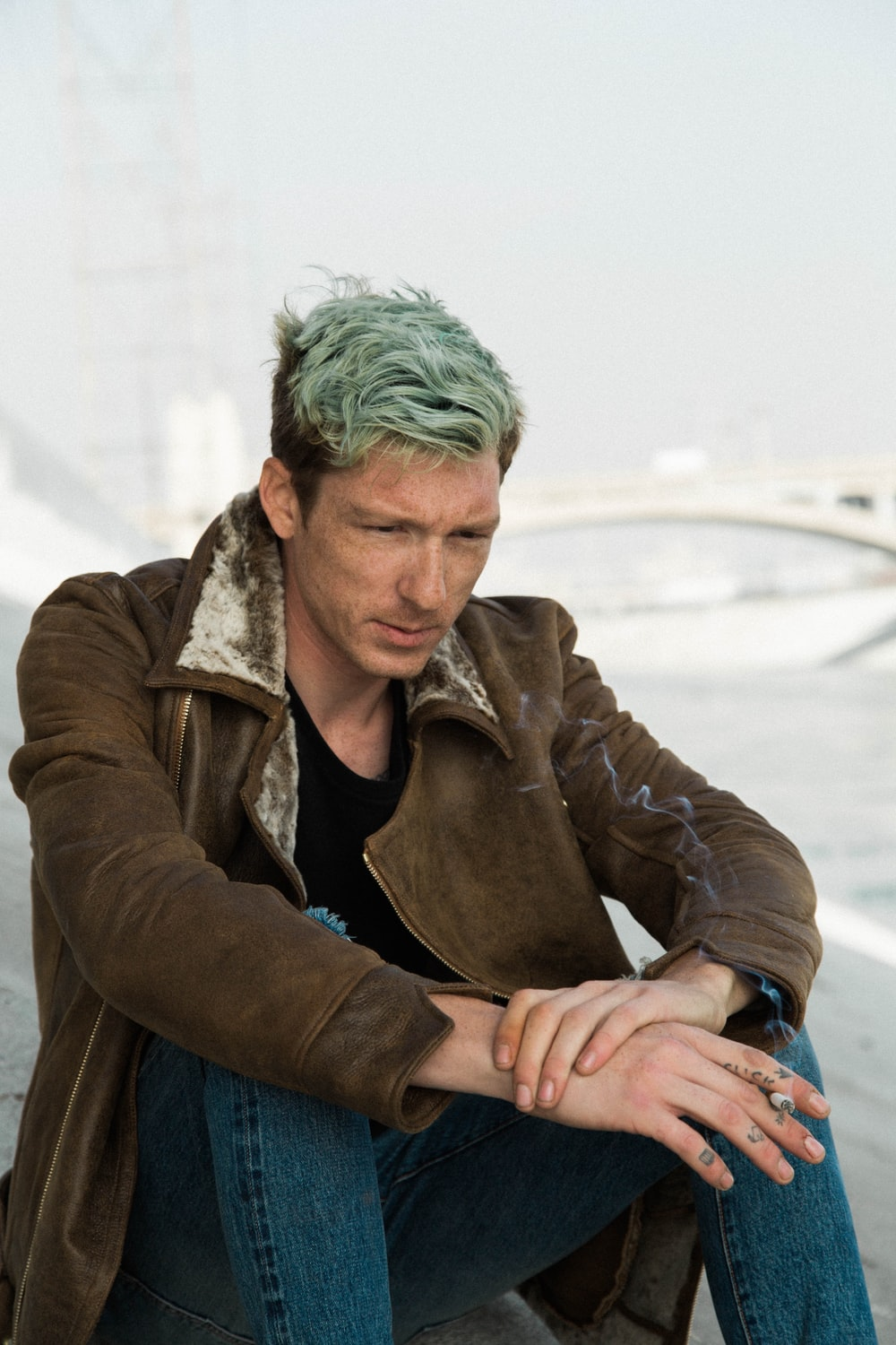 man with green hair in black shirt and brown coat sits on brown sand near white suspension bridge