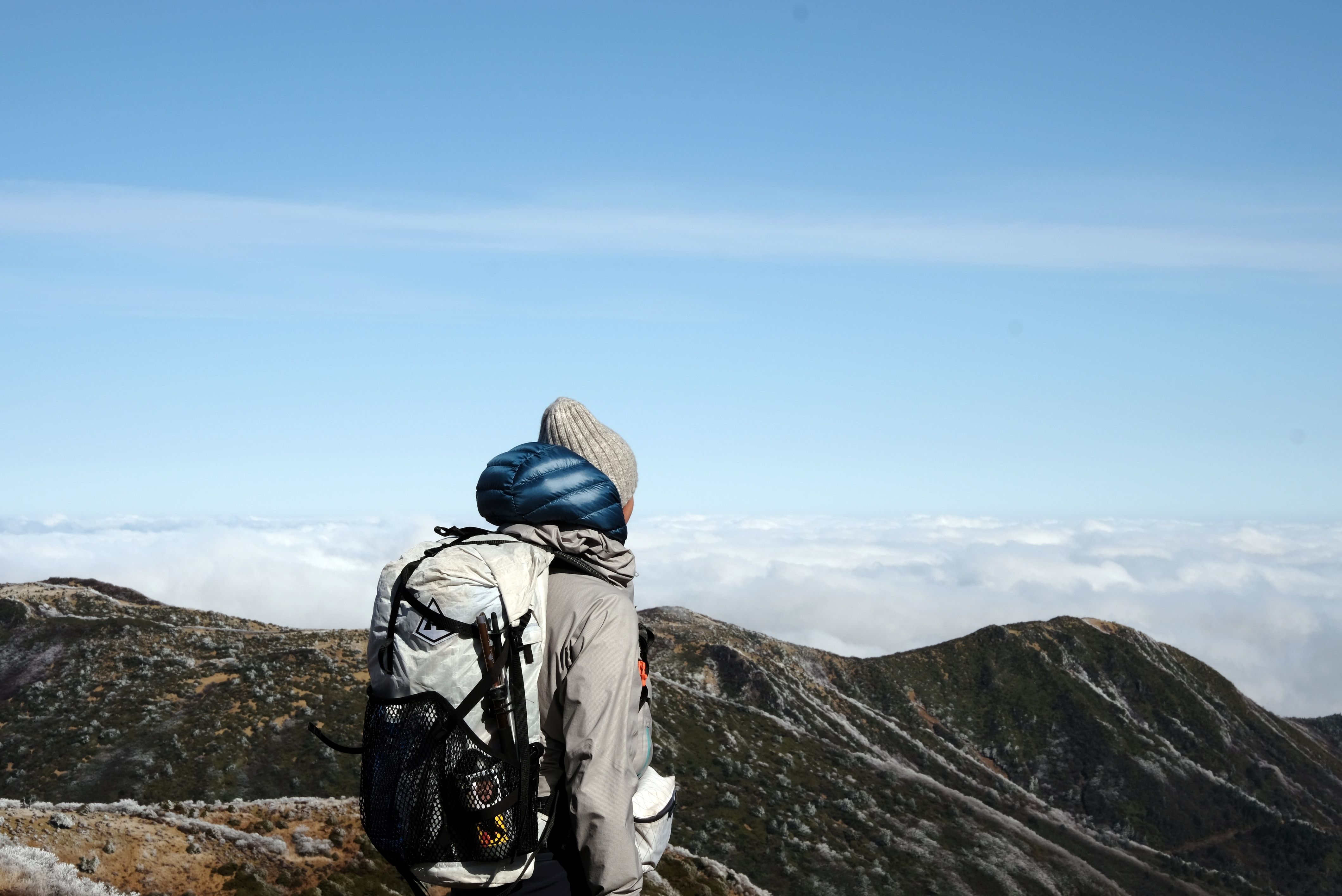 person standing on brown mountain under blue and white sky