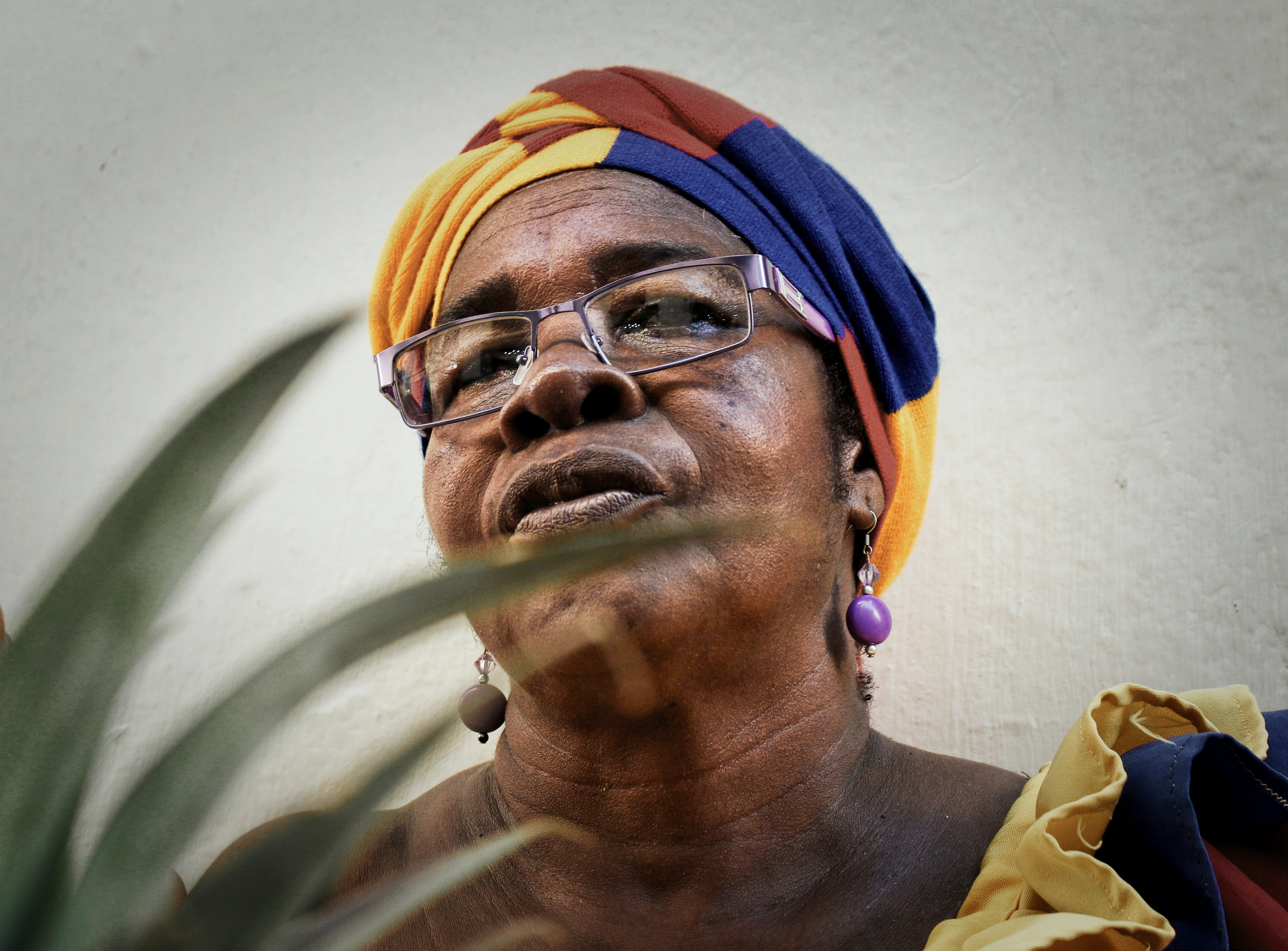 woman wearing yellow, blue, and brown headdress and eyeglasses