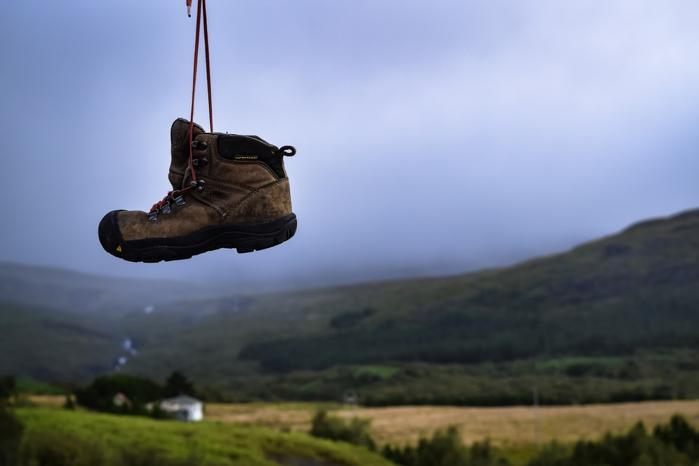 brown and black boot hanging overlooking mountain and field view during daytime