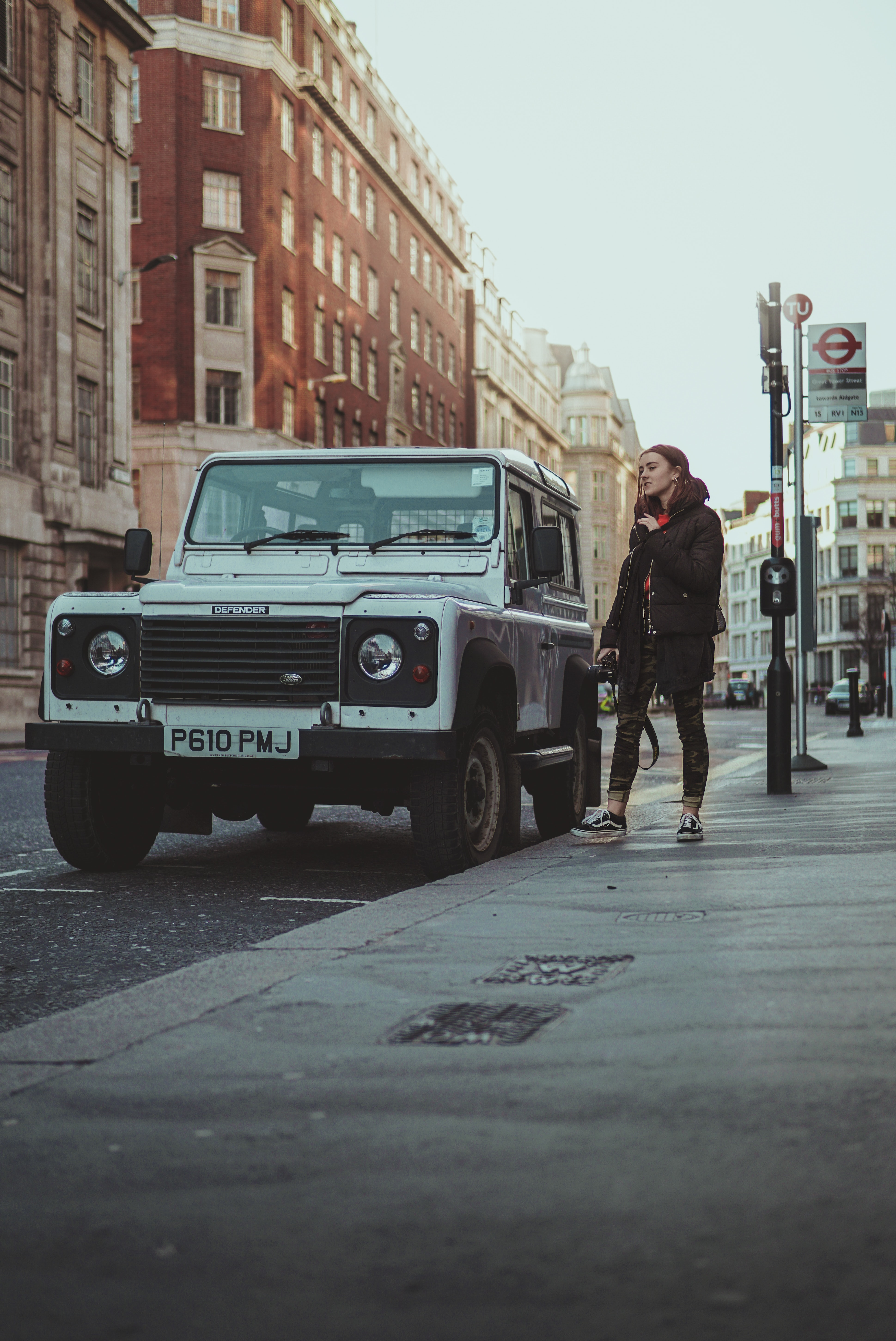 woman standing beside white SUV on street at daytime