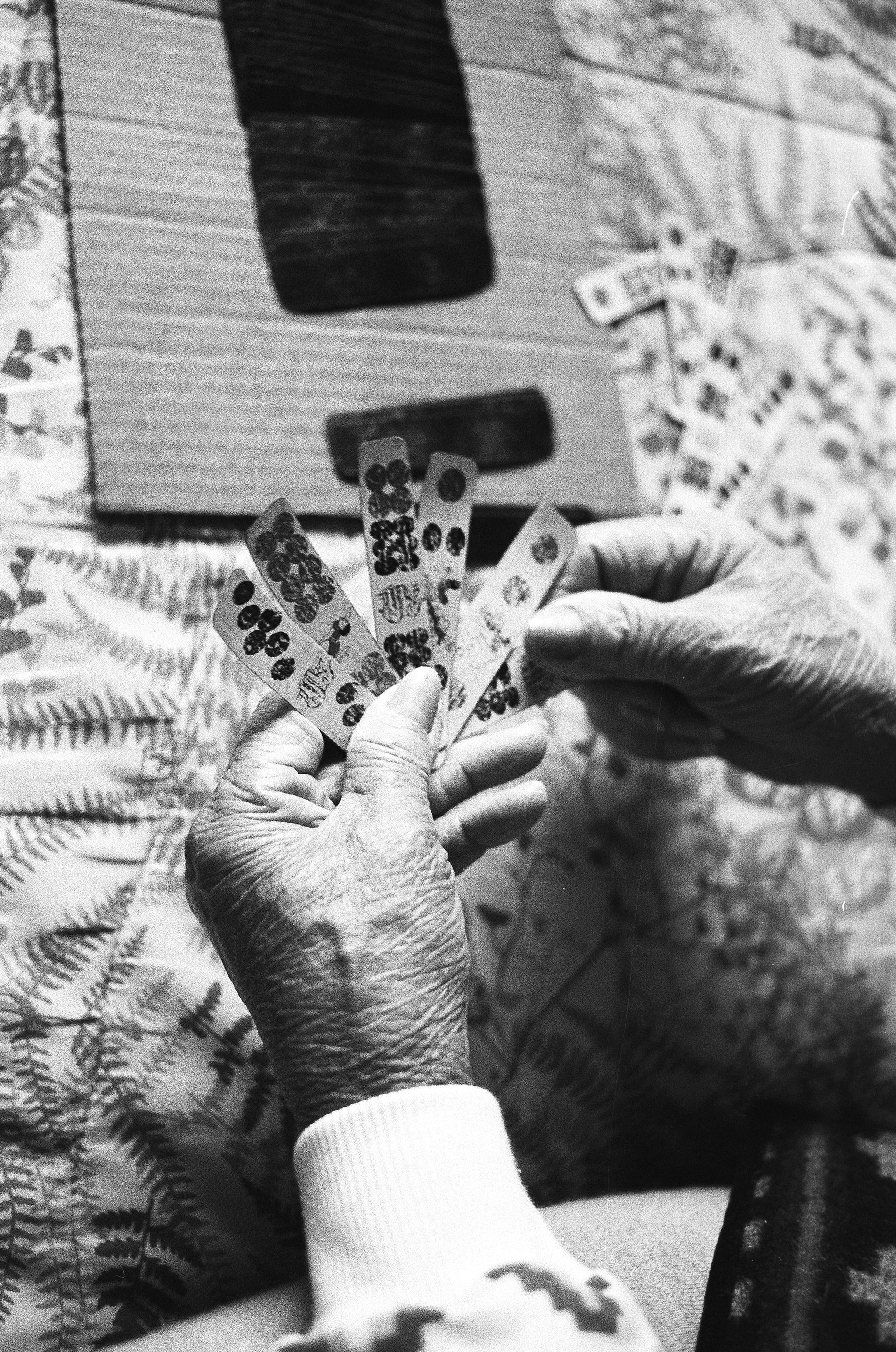 grayscale photo of person holding game chips