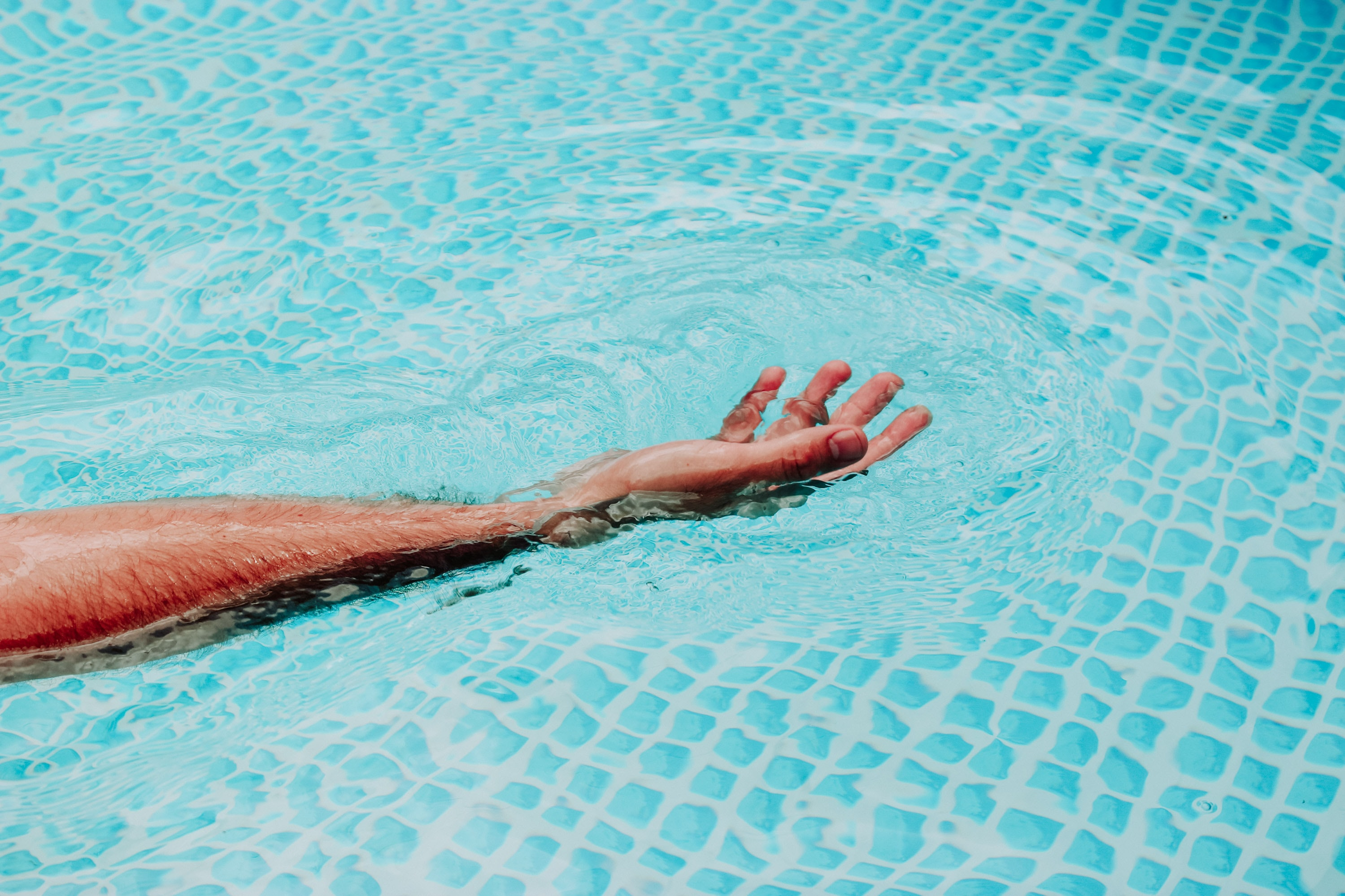 person's hand on above body of water during daytime
