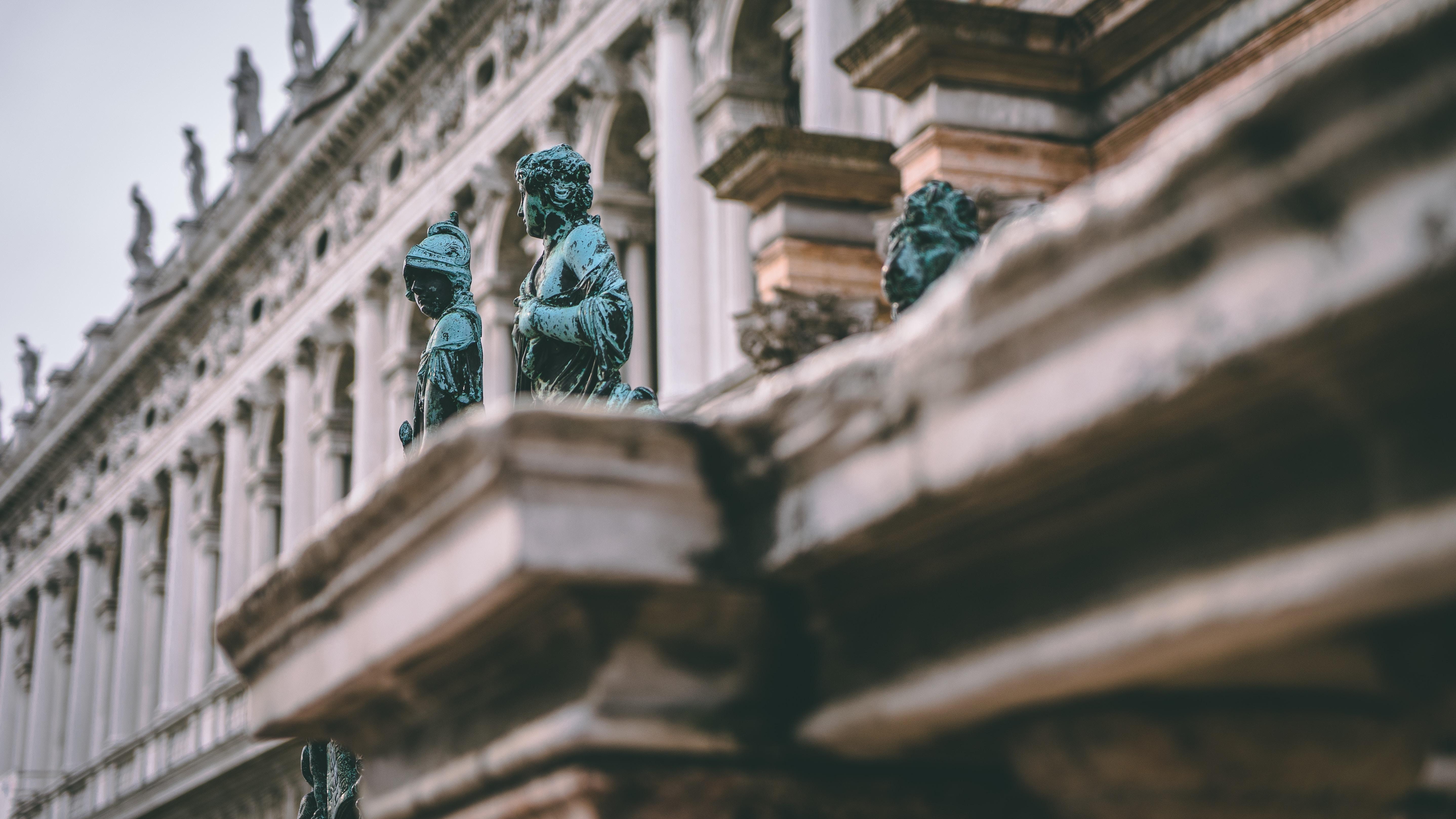 human statues near white building