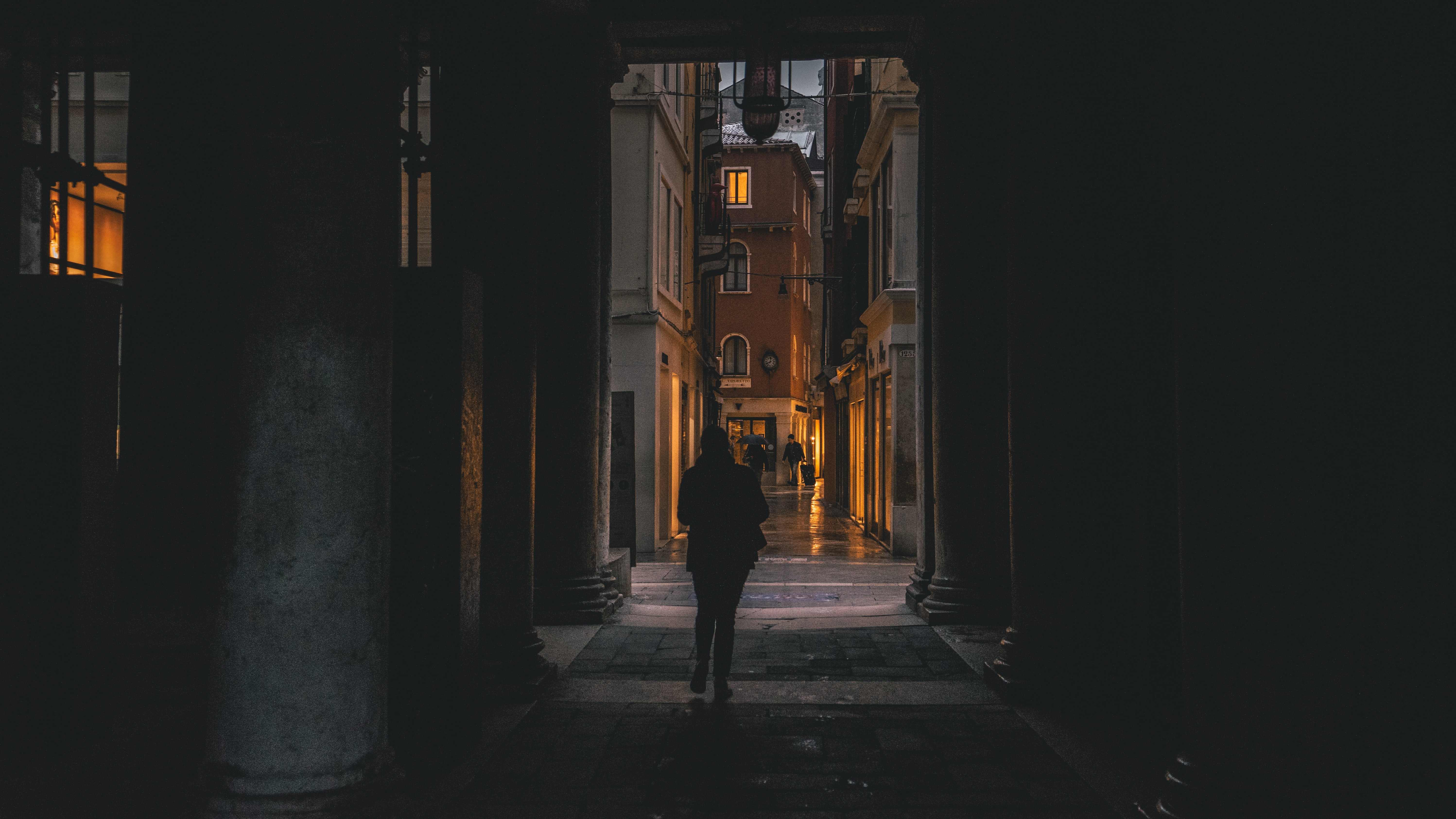 photography of person walking inside archway