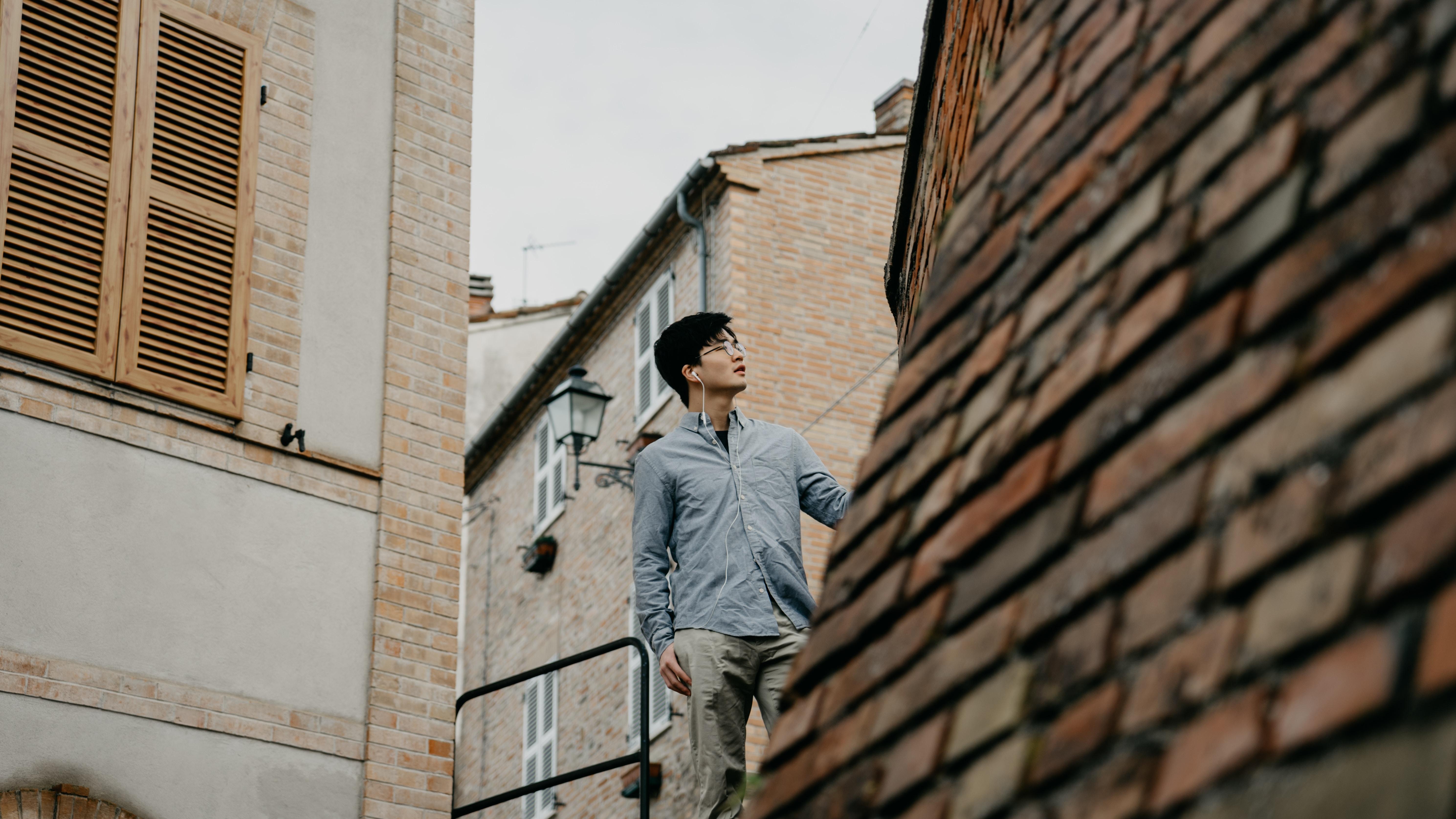 man standing near brown concrete house