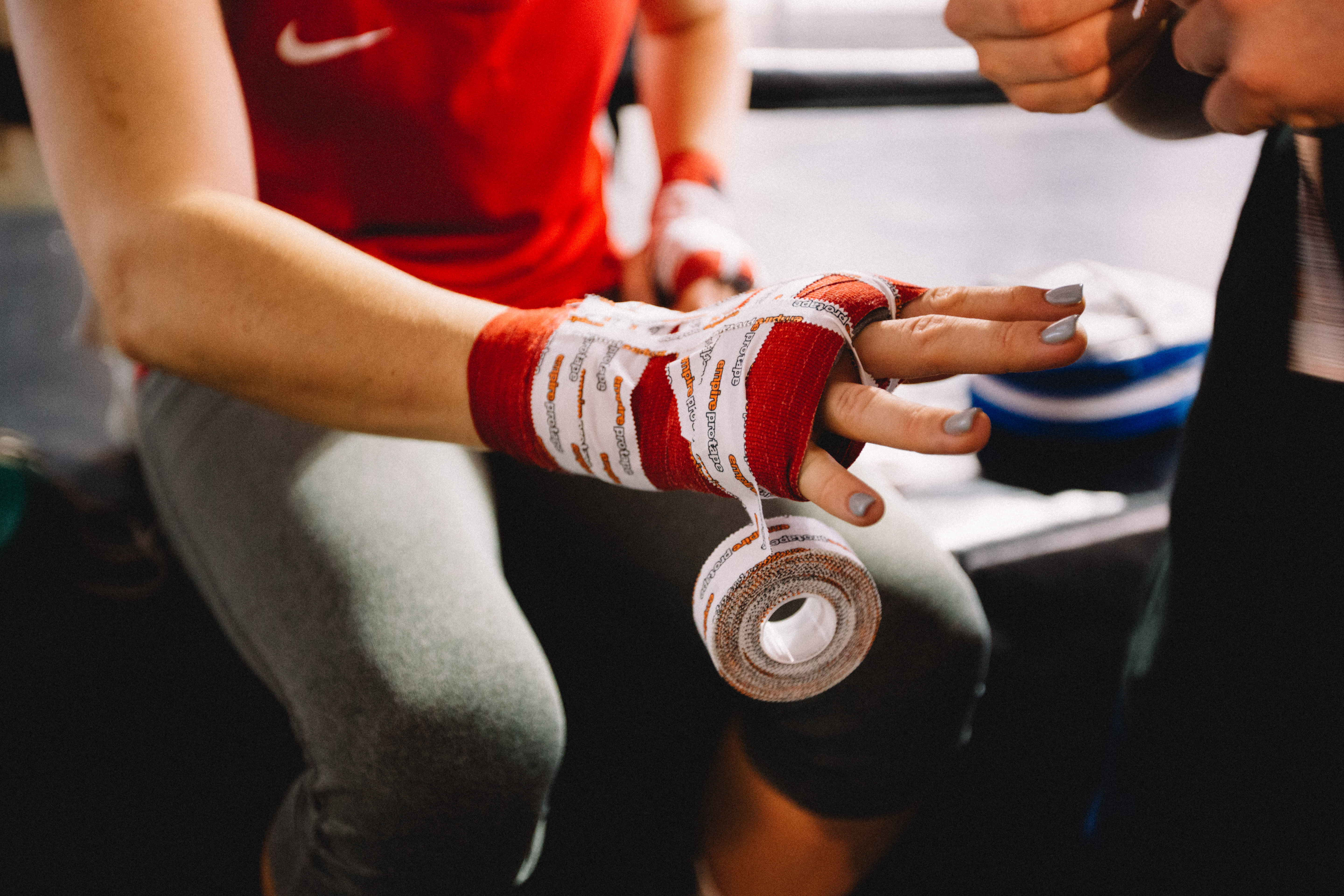 Female boxer getting ready to fight. Love the detail of her finger nails whilst getting wrapped up to punch! Lookout!