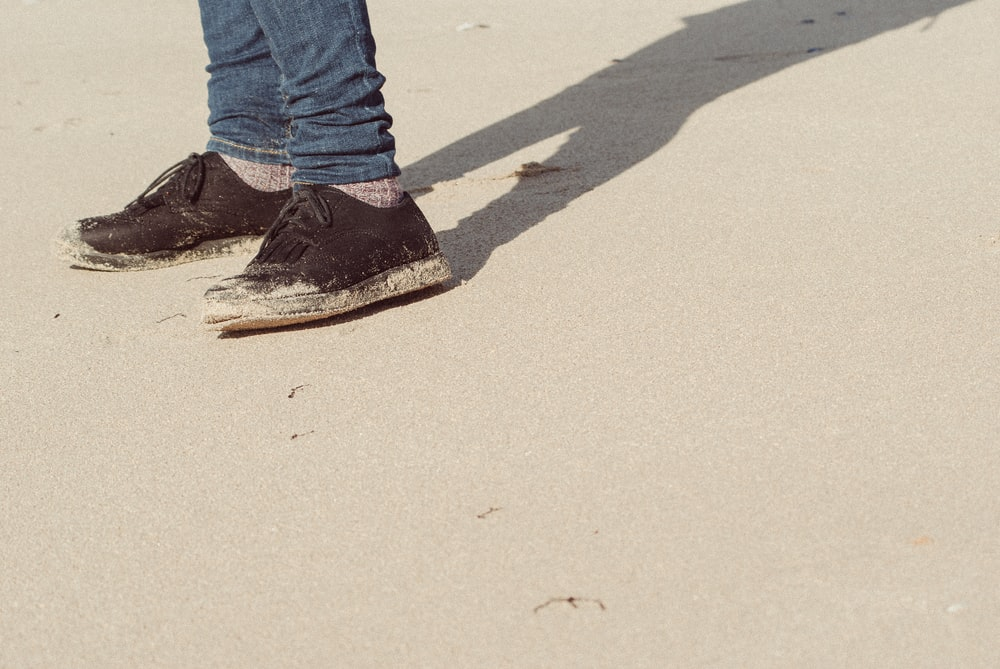 person wearing black-and-white low-top sneakers on sand