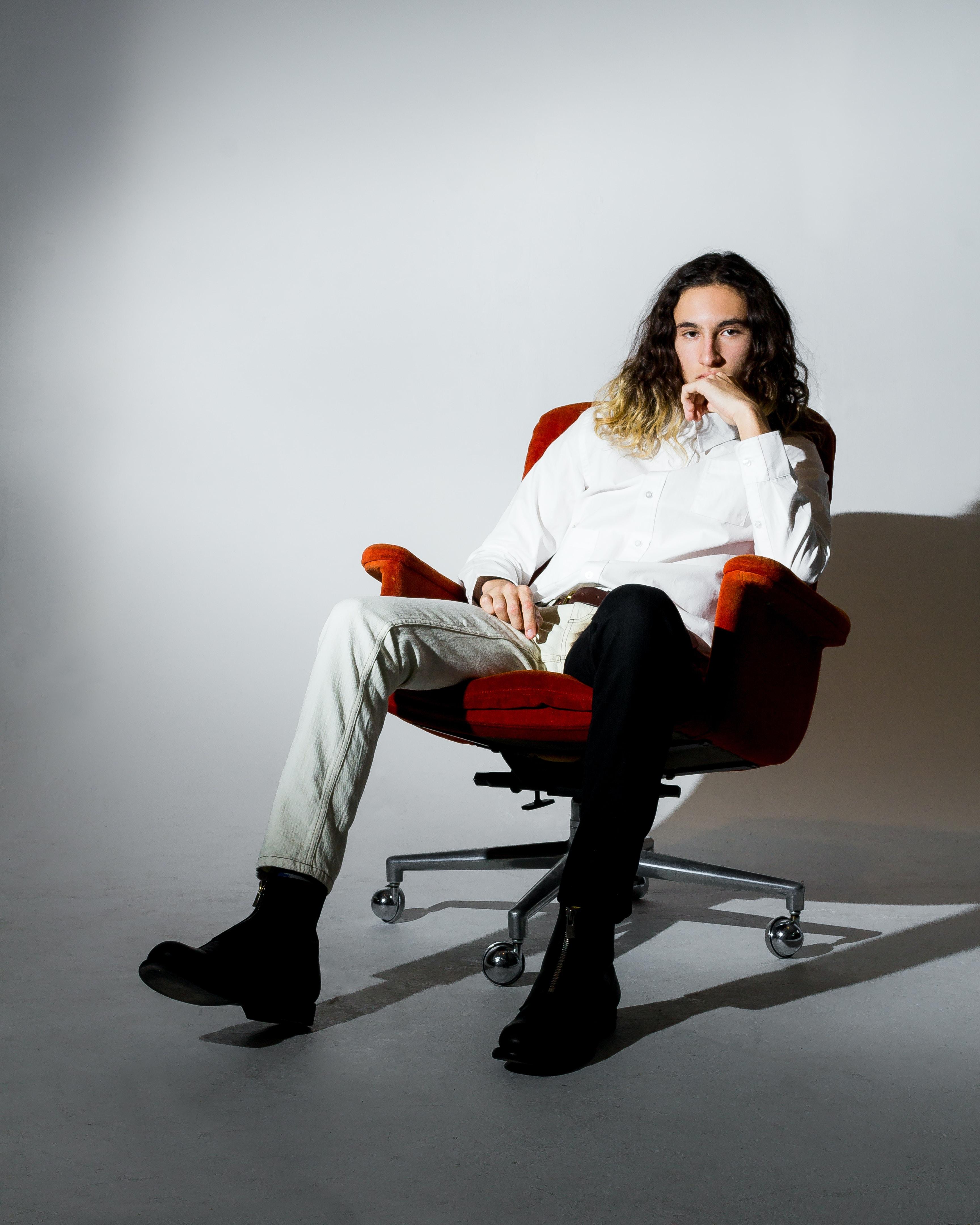 man sitting on rolling chair inside well-lit romo