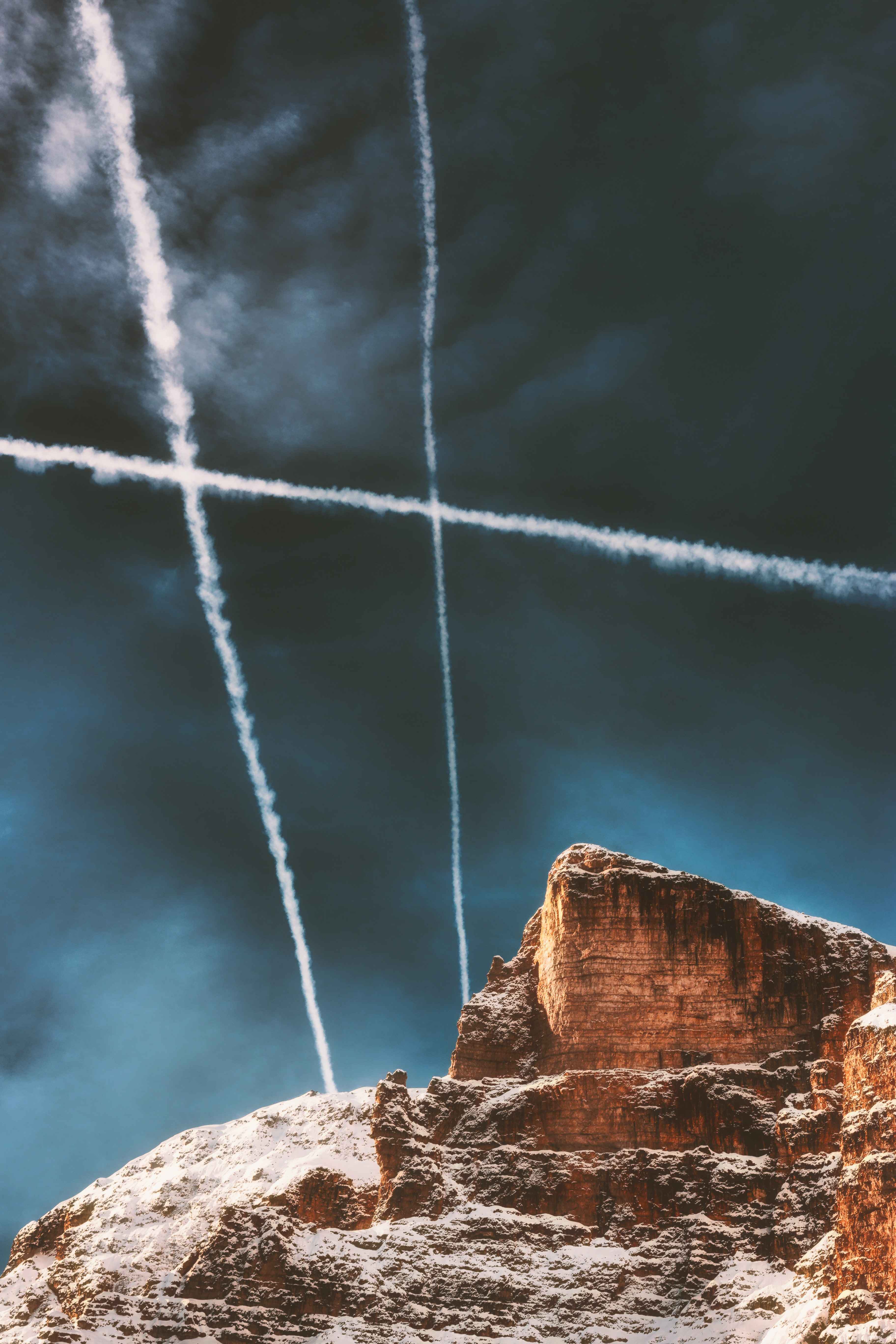 brown rock formations under contrails