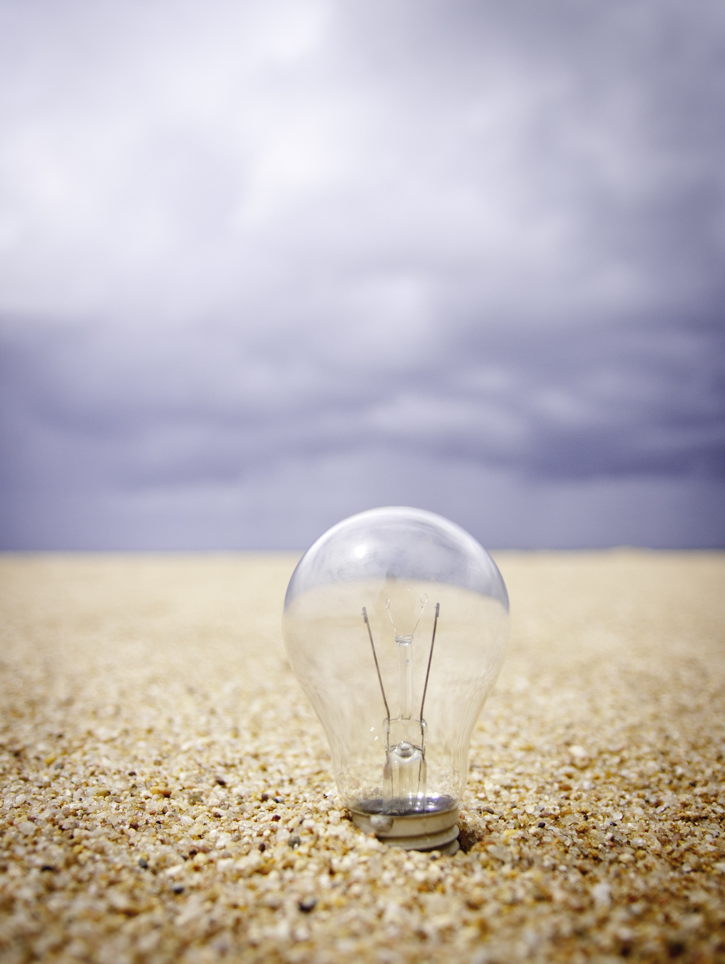 clear glass light bulb on sand during daytime