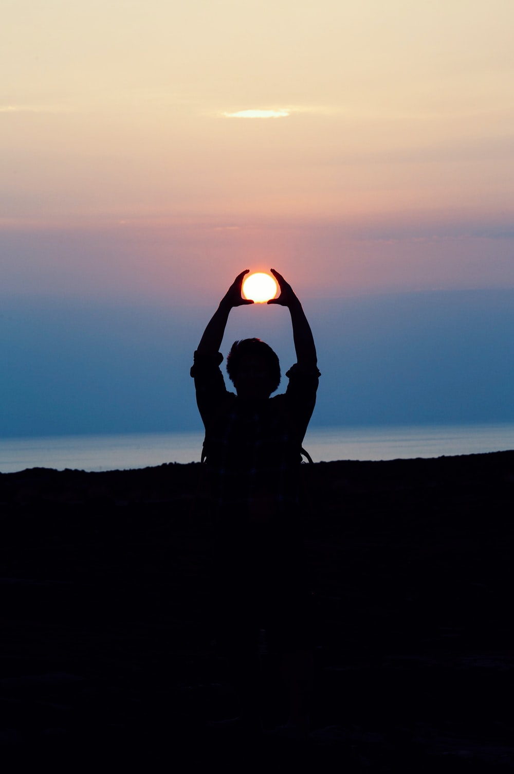 silhouette of person with both hands over his head tracing the sun during golden hour photography