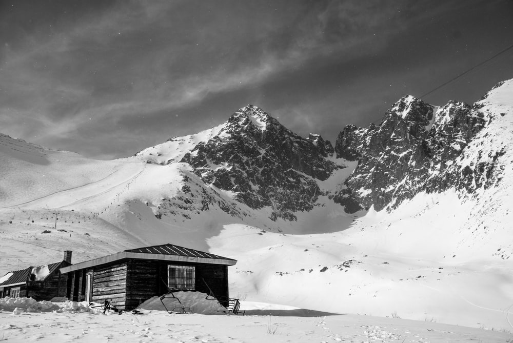 grayscale photo of house on mountain covered with snow