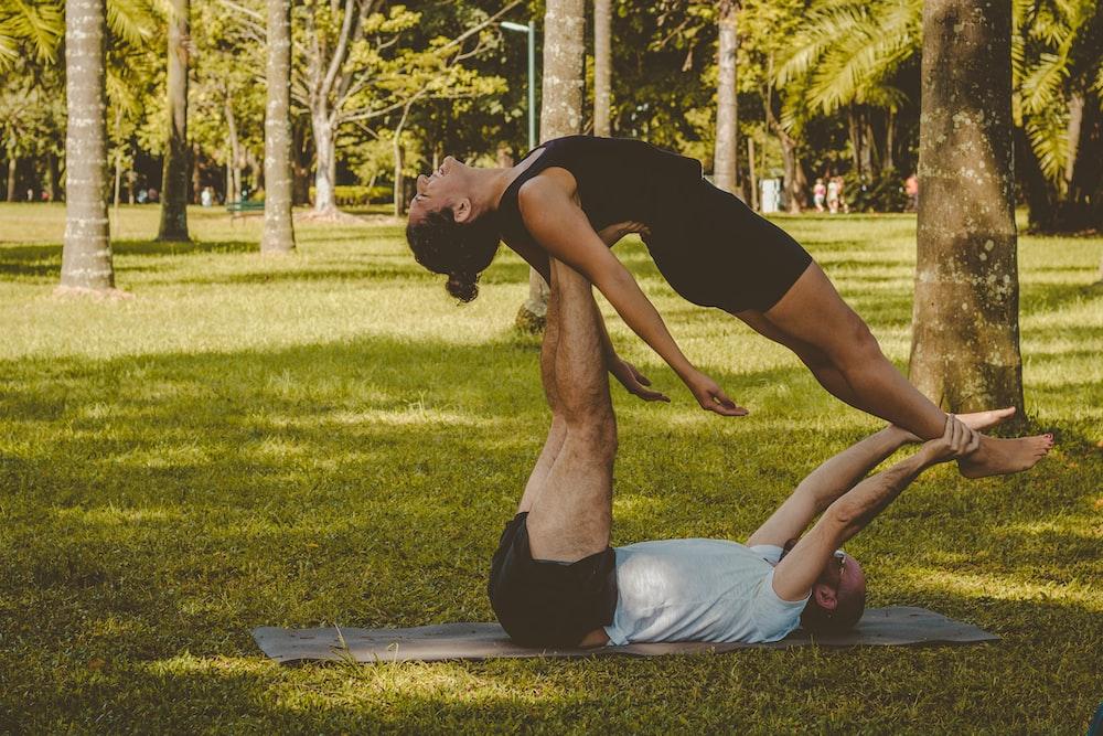 man lifting woman while lying on man foot at daytime