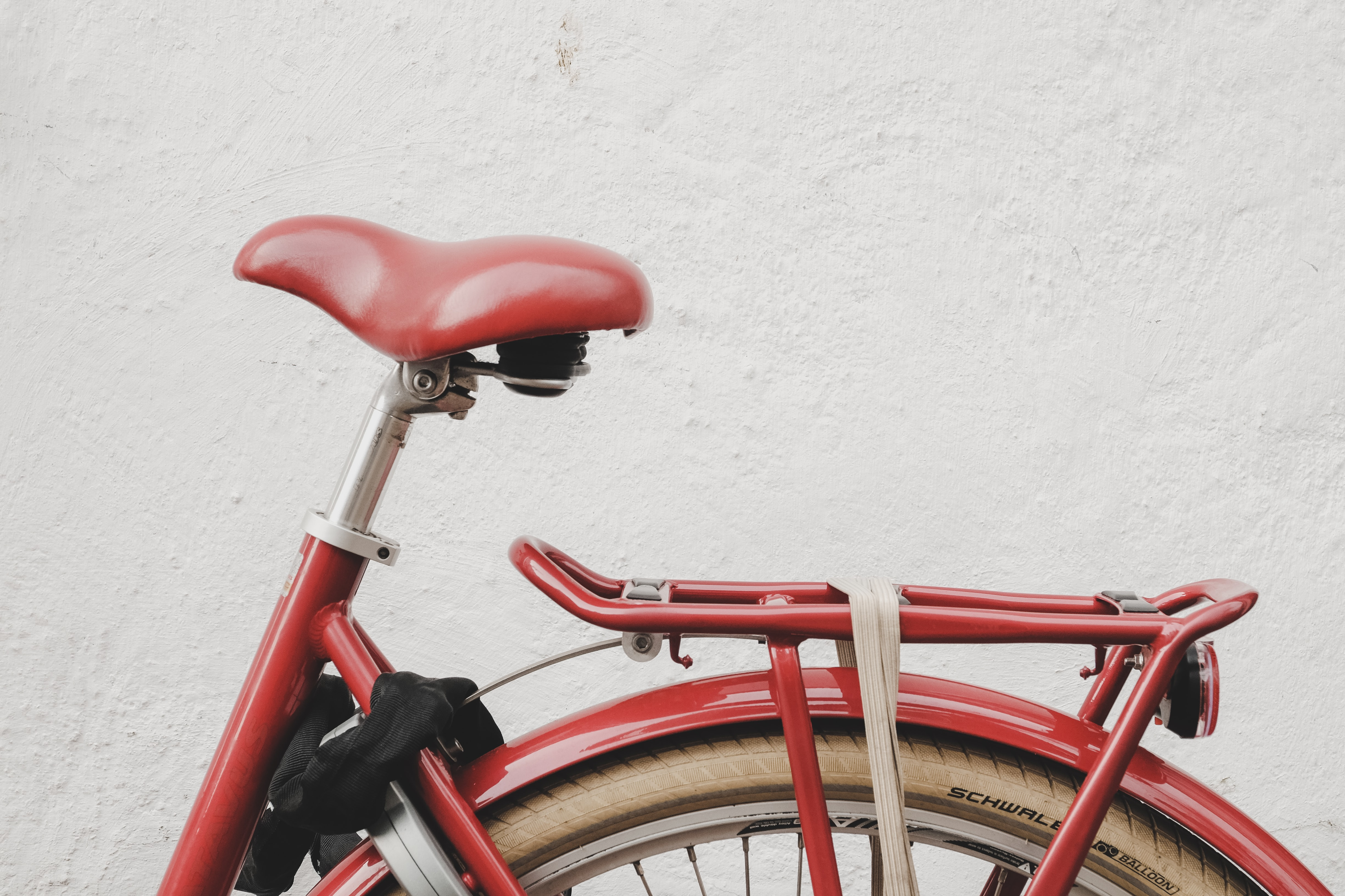 red bicycle near white wall