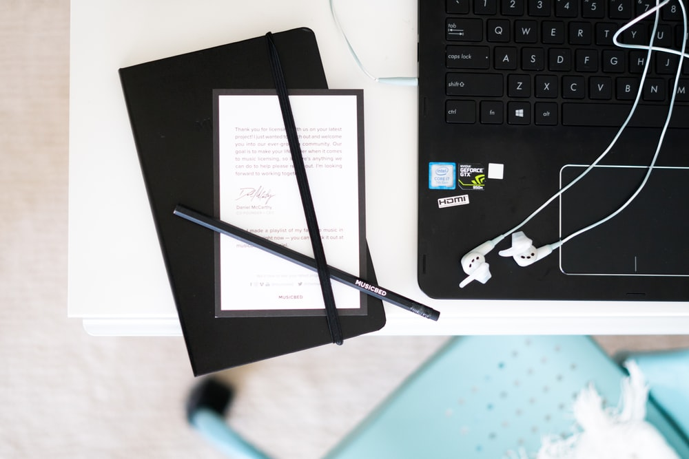black pens beside laptop computer placed on table