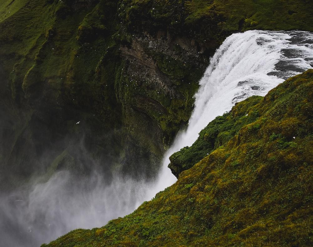 flowing waterfalls near green mountains