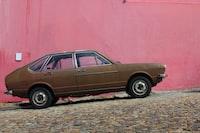 brown 5-door hatchback park beside red wall