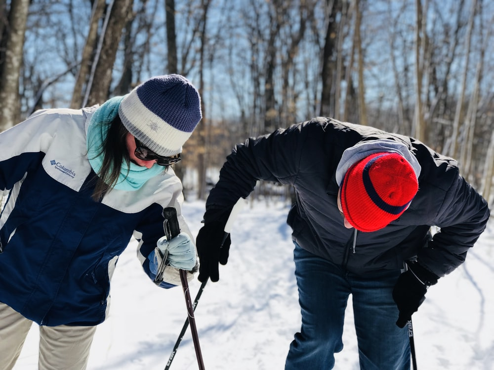 two people holding black ski pole looking down during daytime
