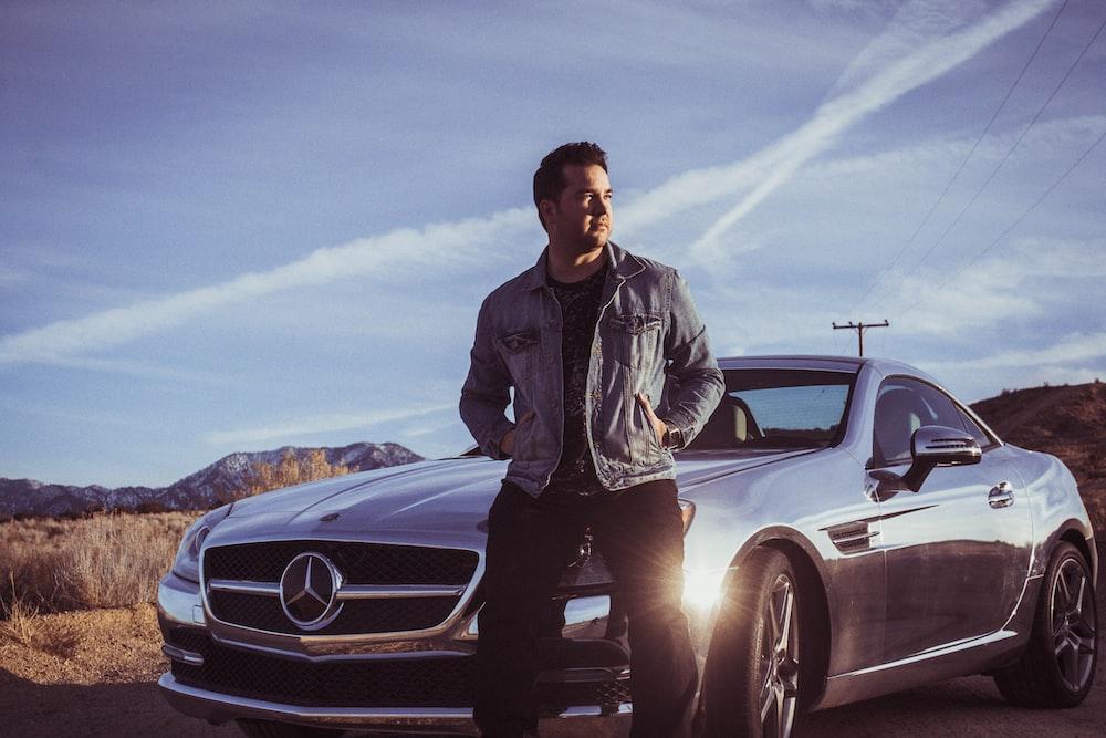 man sitting on Mercedes-Benz car's hood