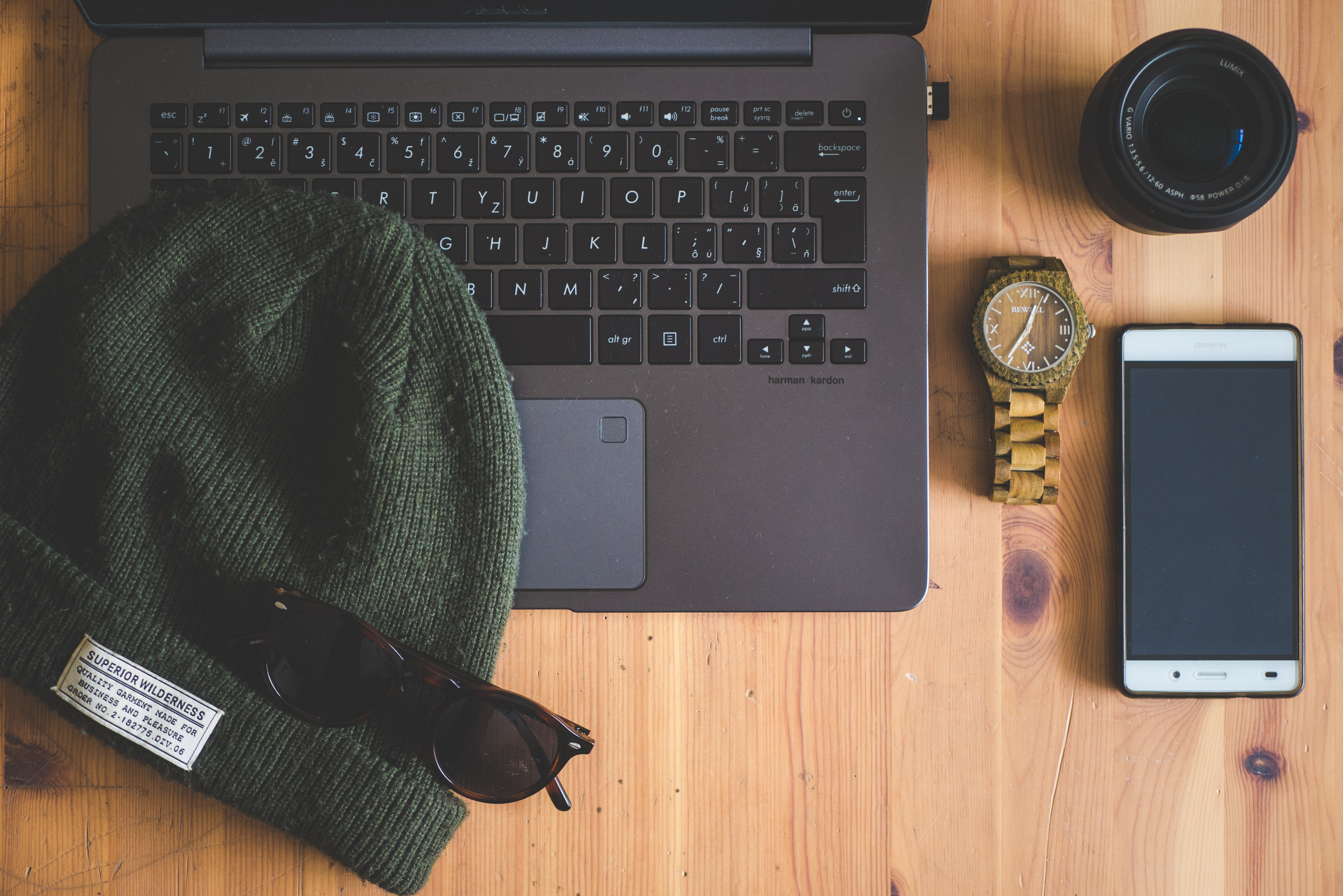 green knit cap on laptop near watch, smartphone, and camera lens