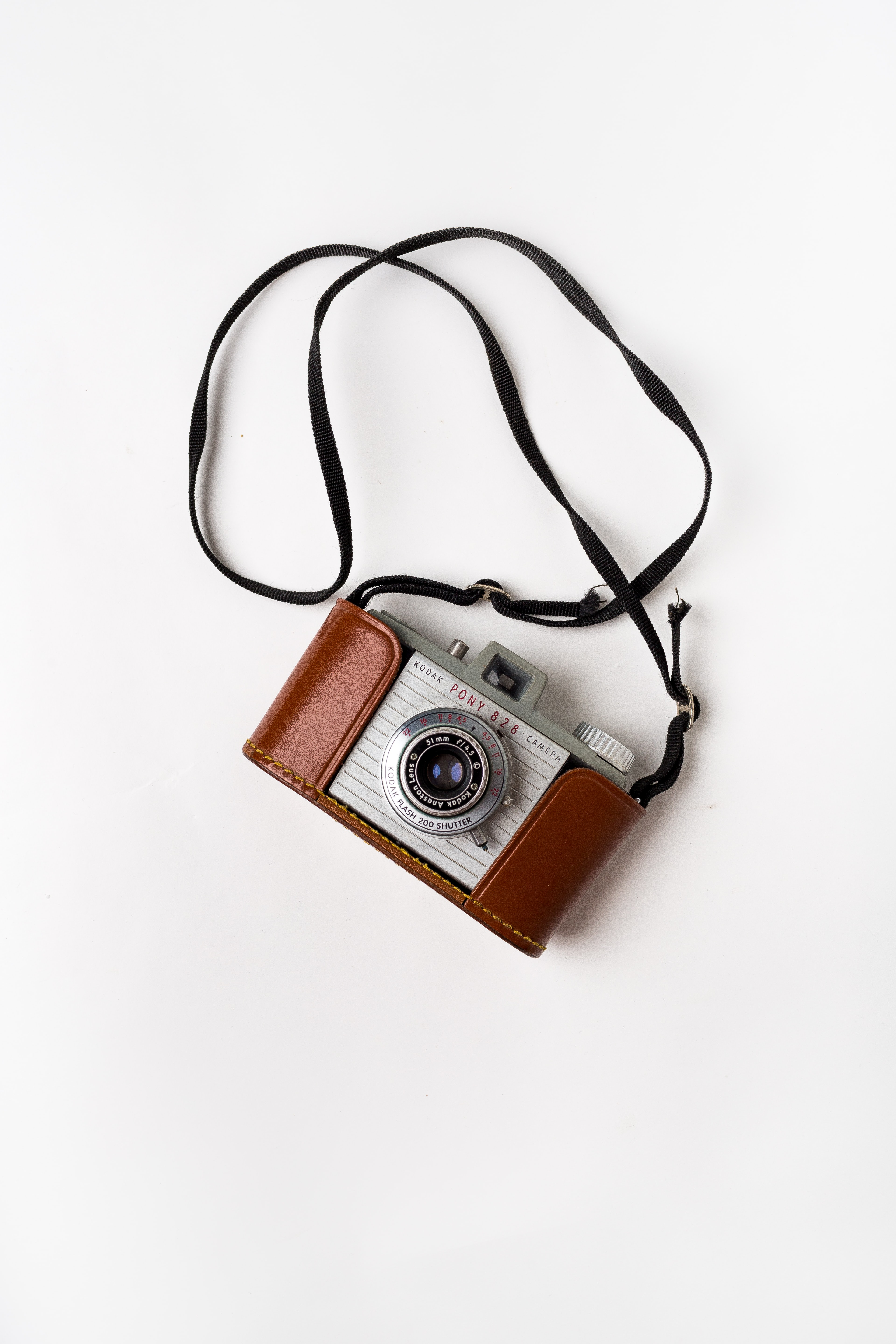 brown and gray SLR camera on white surface