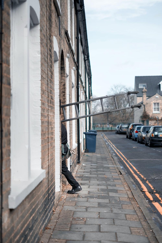 man carrying grey ladder entering brown concrete building during daytime
