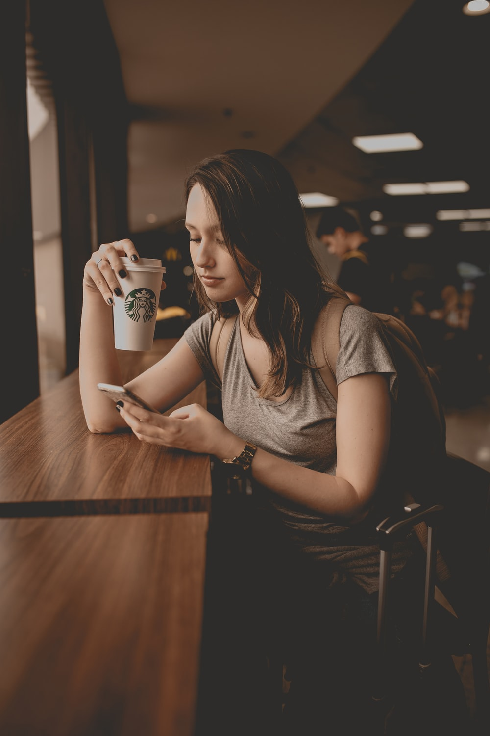 woman holding starbucks disposable cup and smartphone