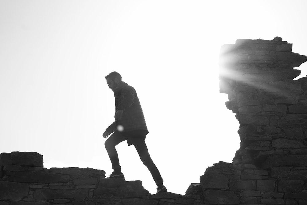 man wearing jacket walking on brick wall