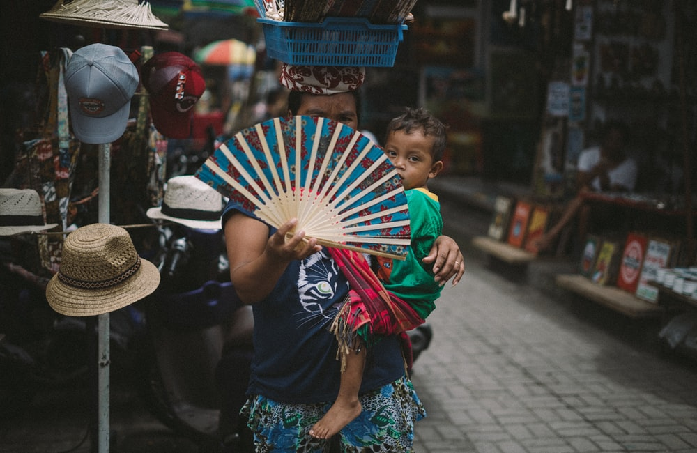 woman carrying baby hiding her face using hand fan