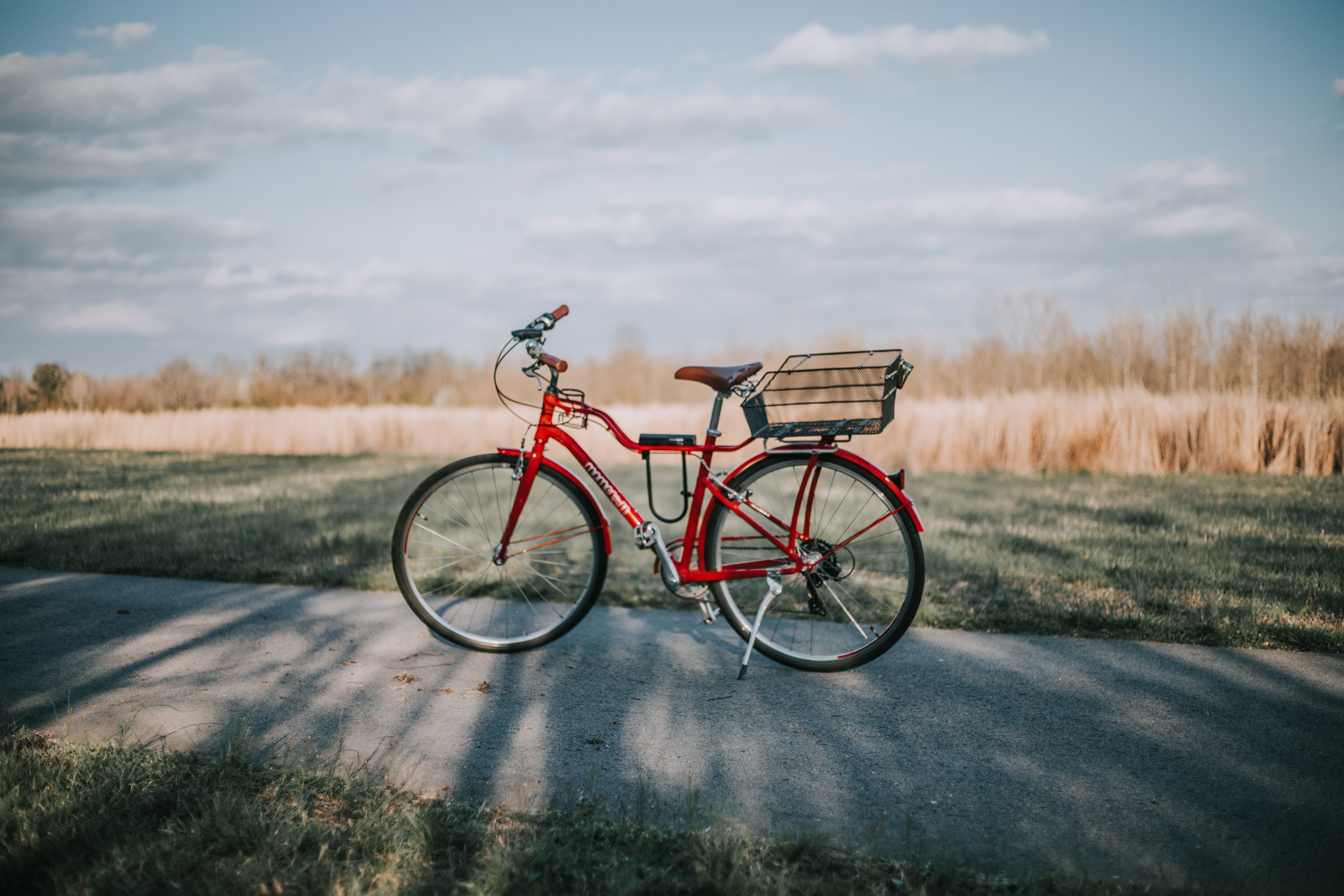 red commuter bike on road in between grass field during daytime