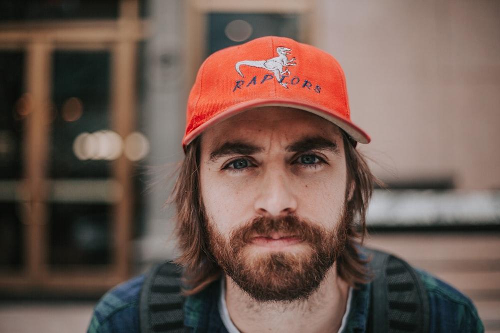 close up photography of man wearing orange Raptors cap