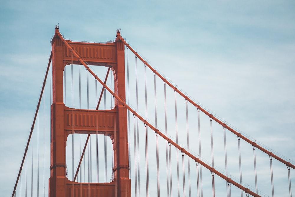 brown suspension bridge under blue and white sky