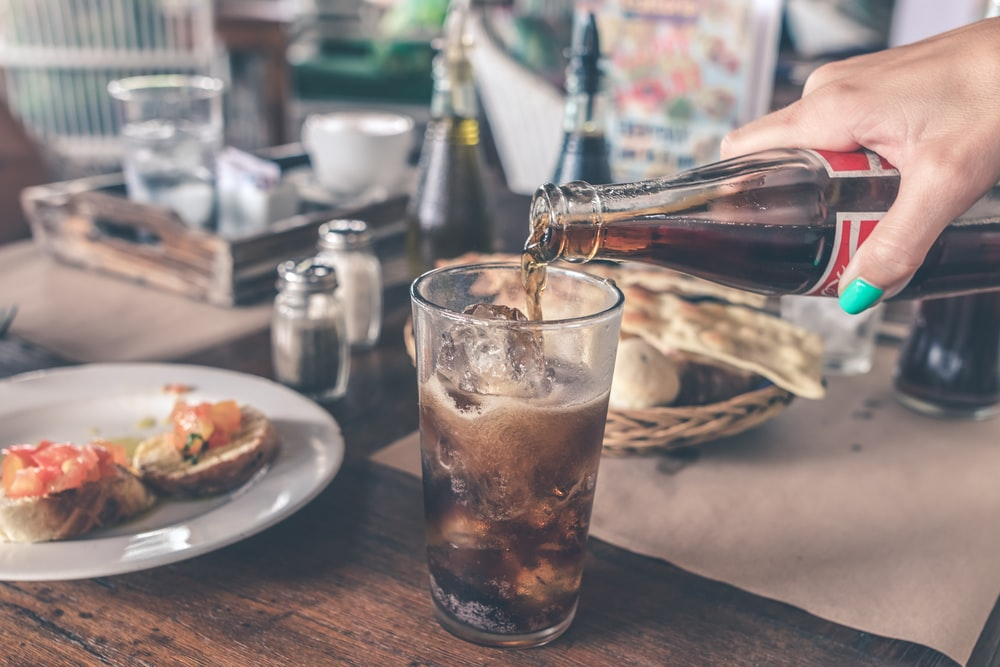 person pouring Coca-Cola soda on clear drinking glass near round white ceramic plate