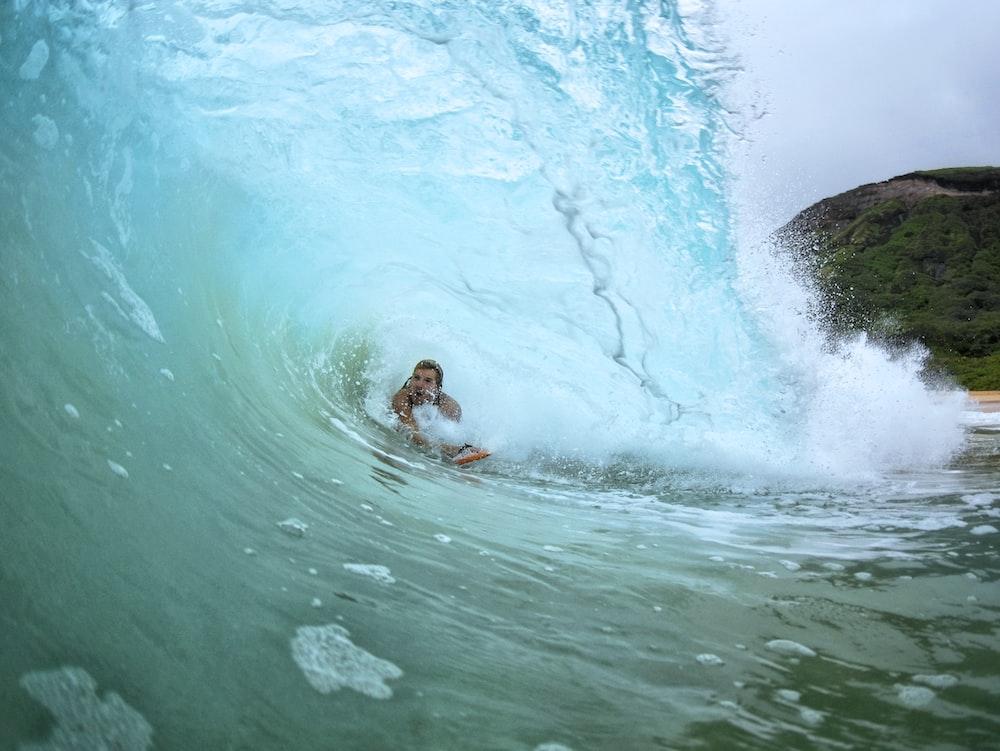 person surfing underneath sea waves