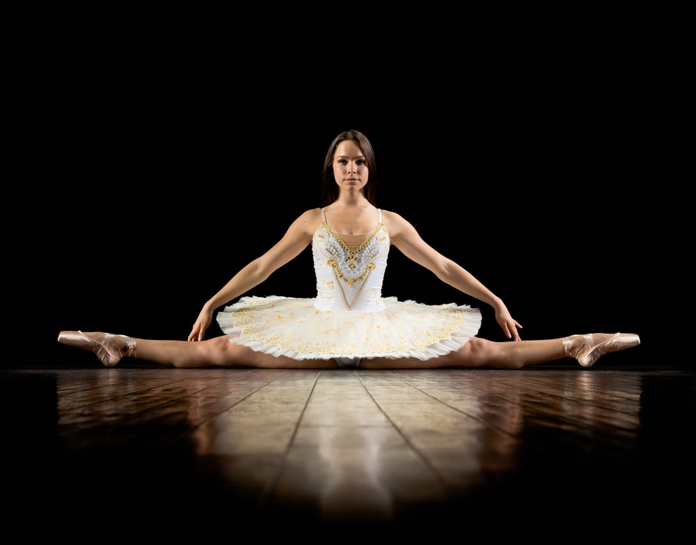 female ballerina splitting on floor in dark room