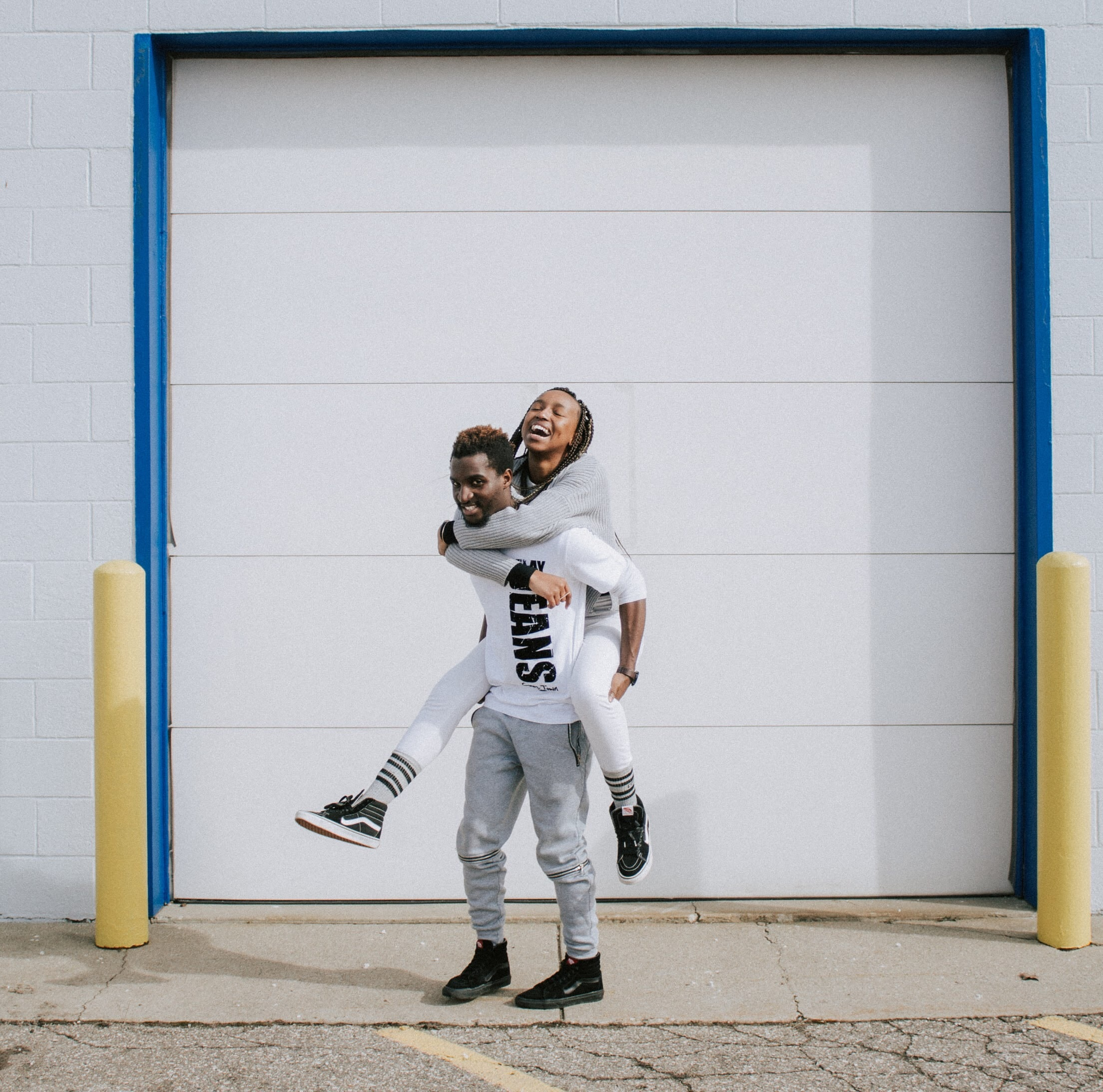 man carrying up woman on his back behind the wall