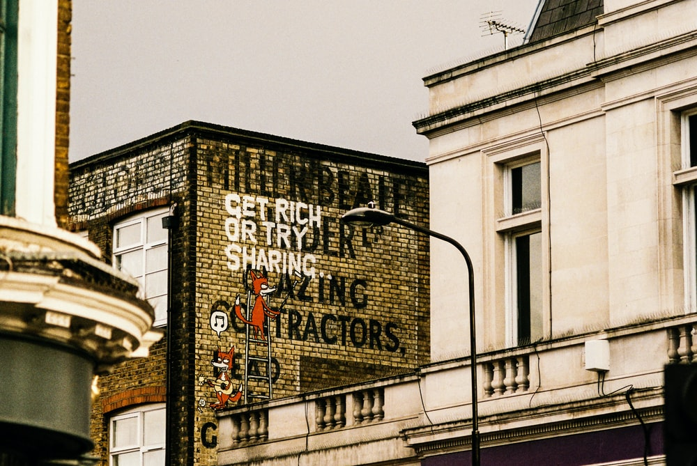 photography of building with get rich or try sharing text printed