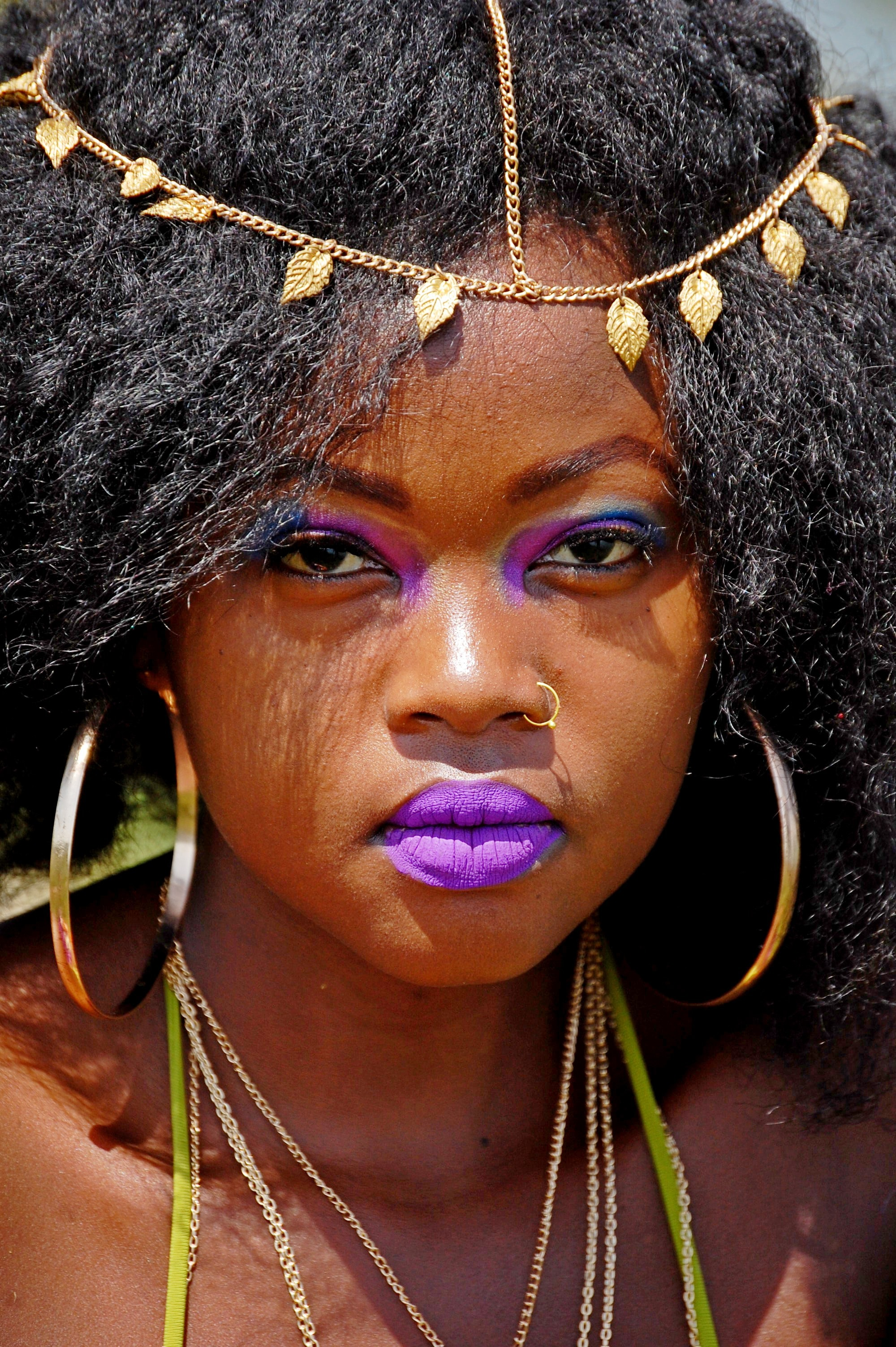 woman with black hair wears gold-colored nose ring, pair of loop earrings and purple lipstick