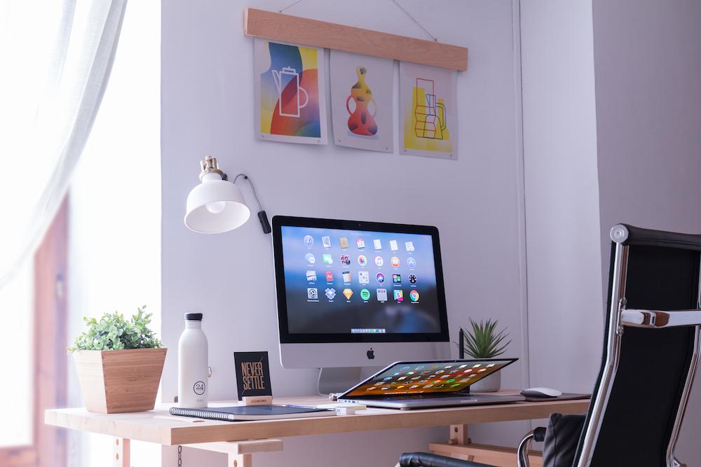 white iMac on brown wooden desk