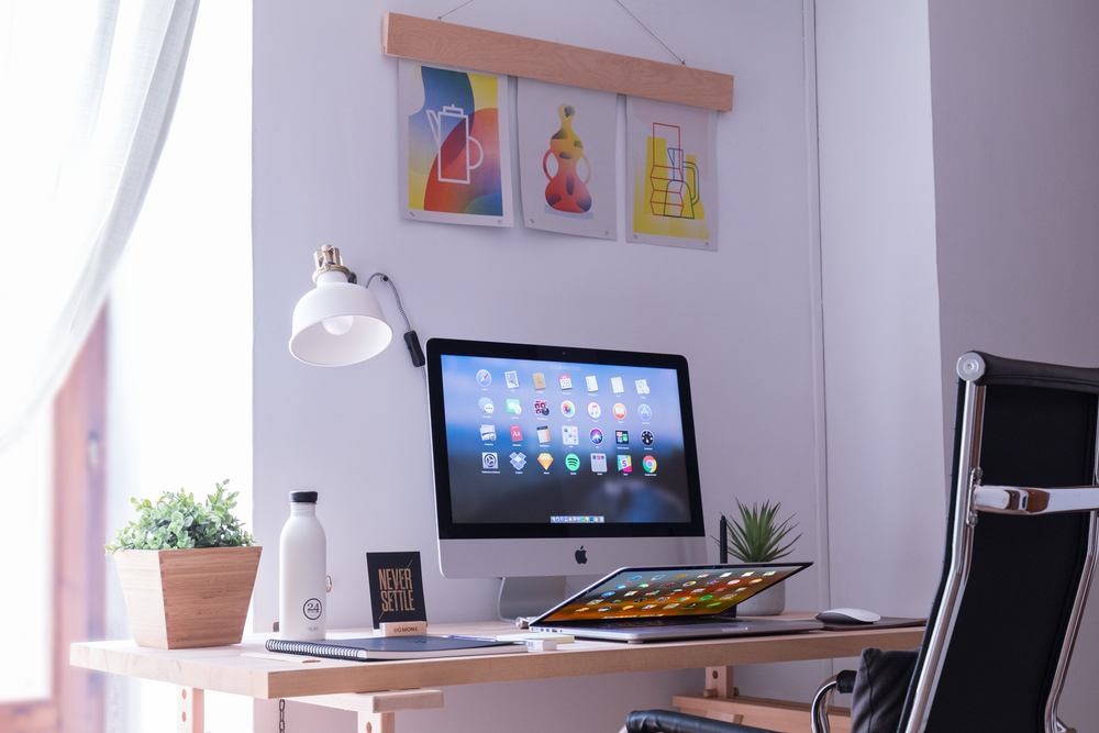 white iMac on brown wooden desk