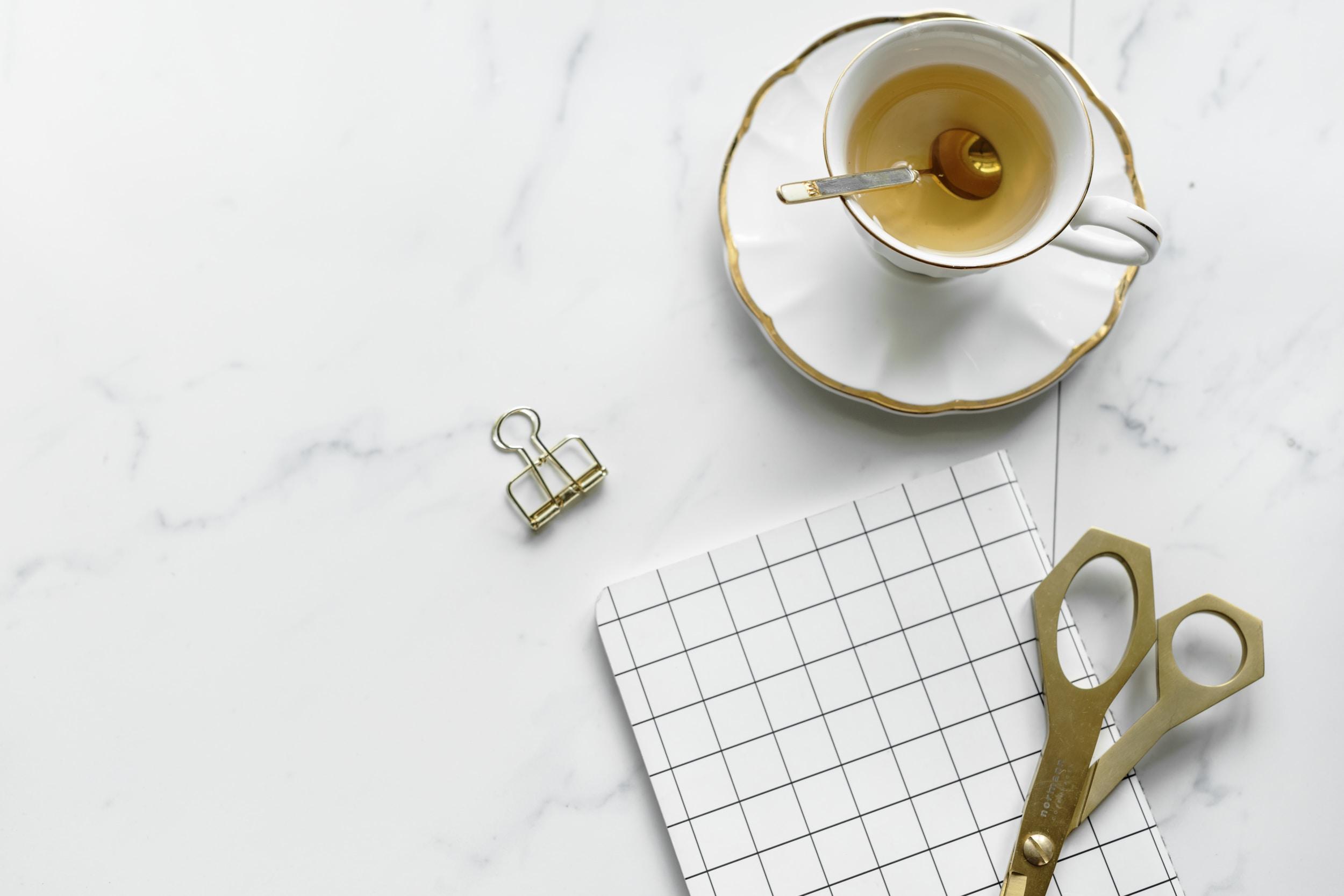 white ceramic teacup on saucer beside shears
