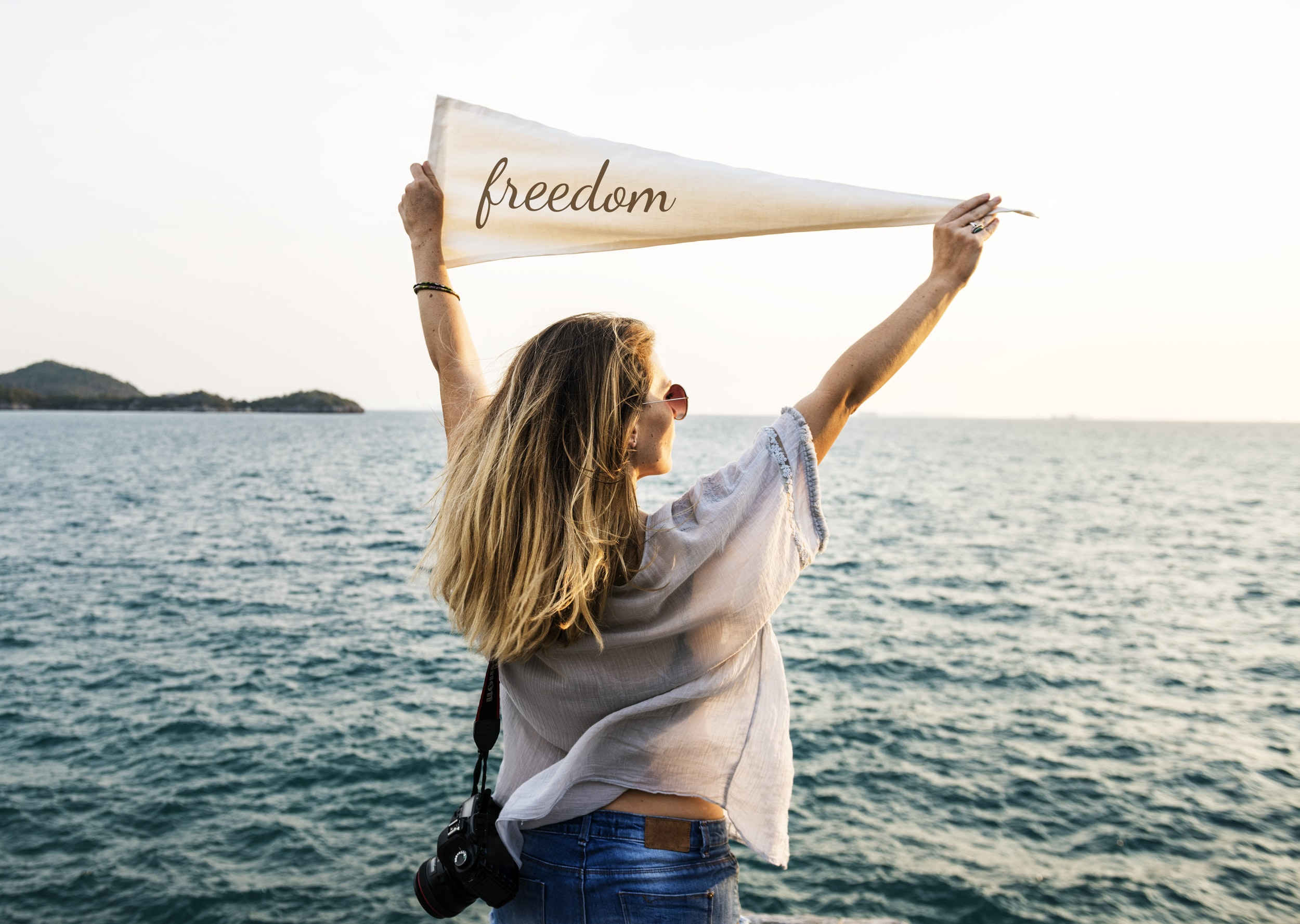 woman holding white freedom pennant flag near body of water