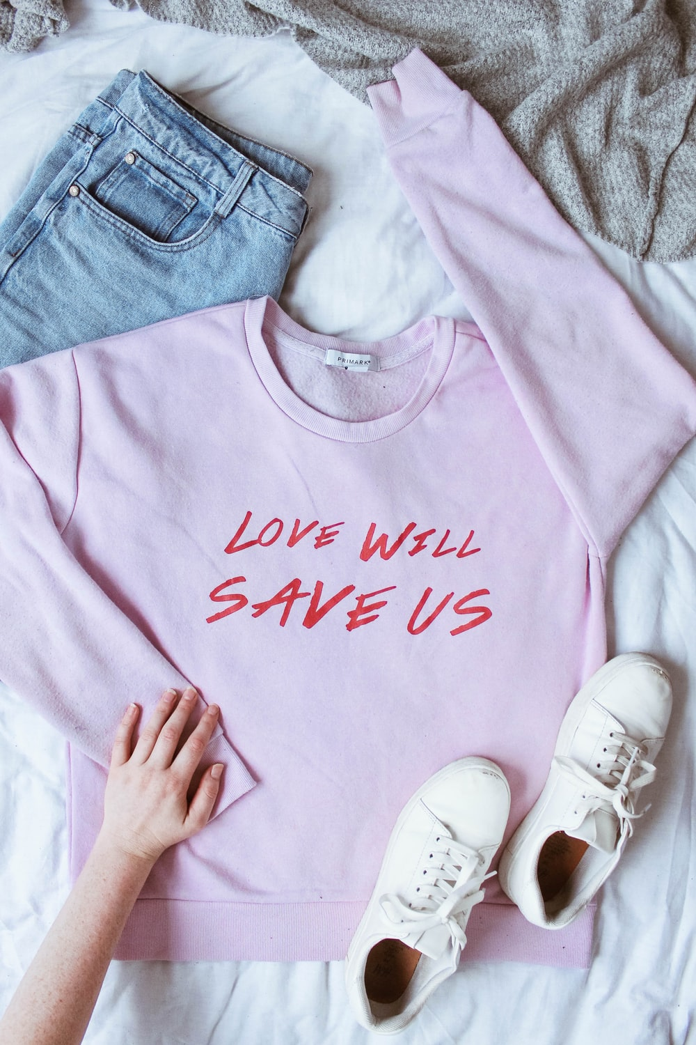 pink long-sleeved shirt on white textile near white low-top sneakers and blue denim bottoms