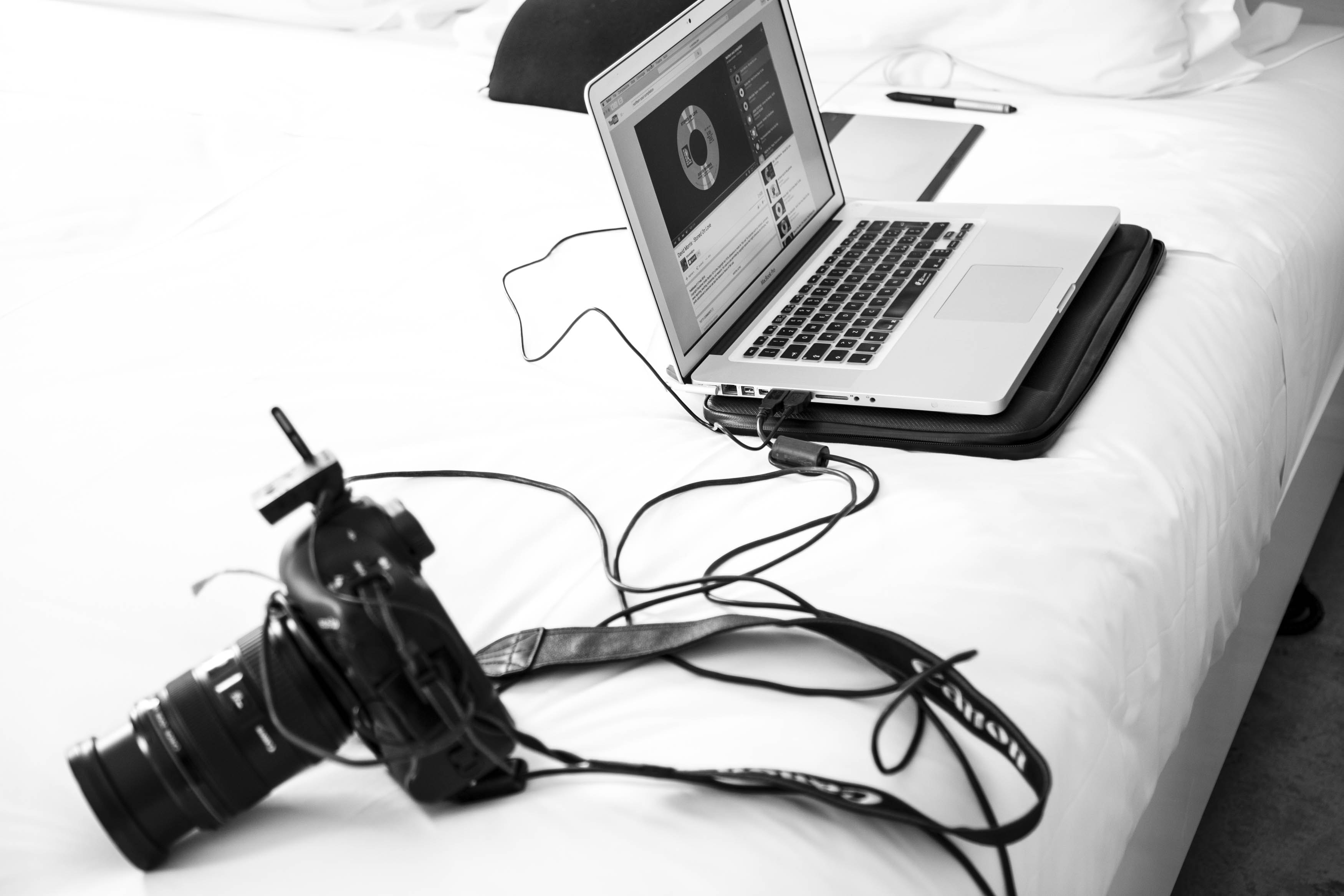 grayscale photography of DSLR camera and MacBook Pro