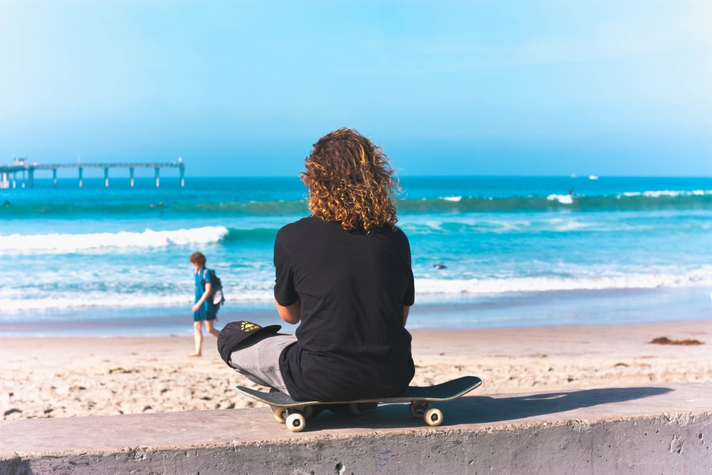person sitting on skateboard with sea shore background