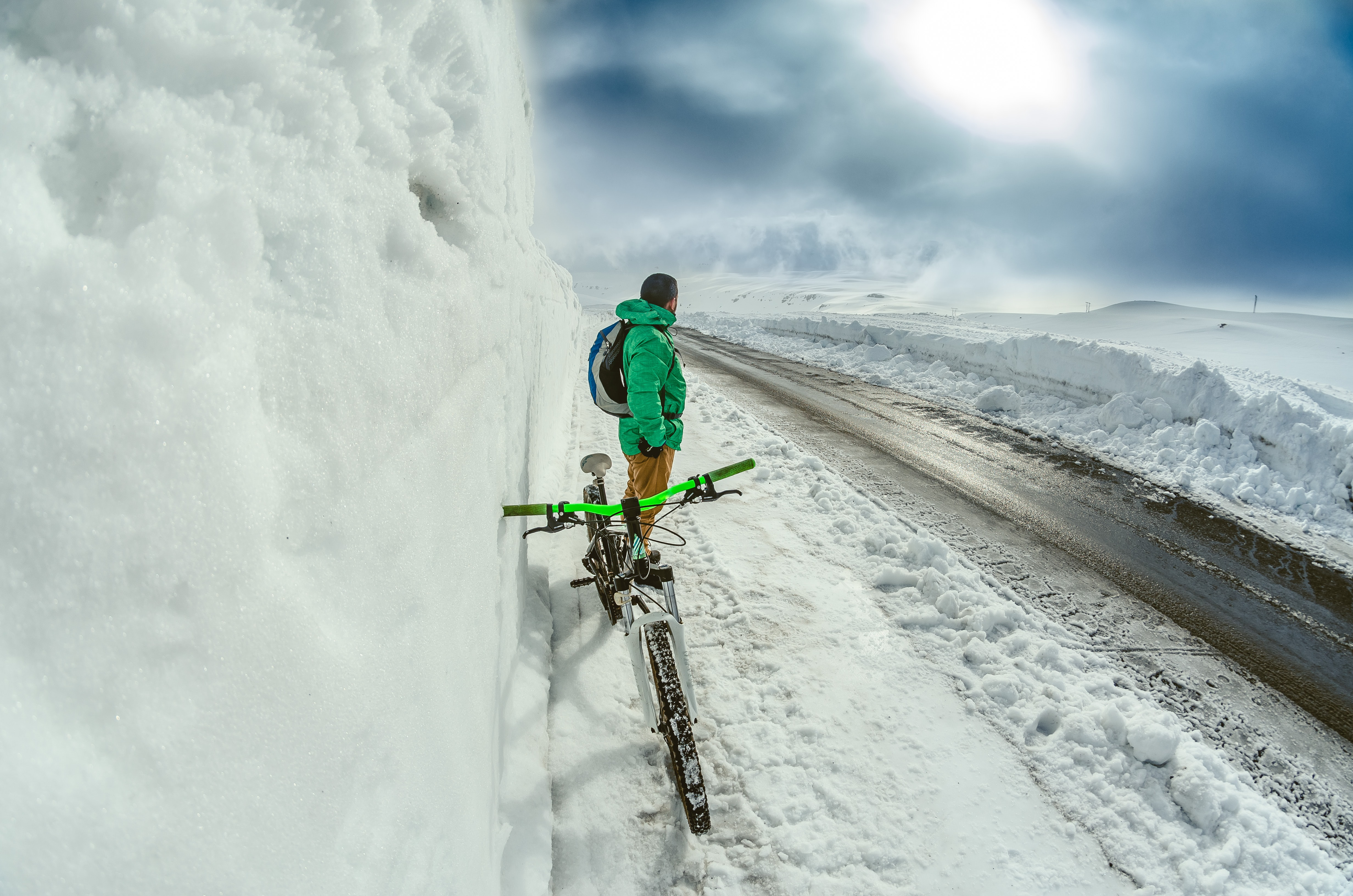 man standing besides green bicycle