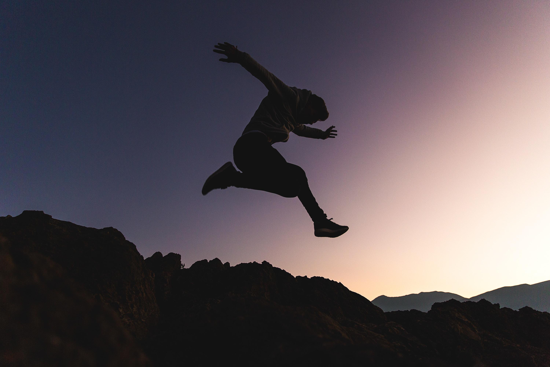 man jumping above mountains
