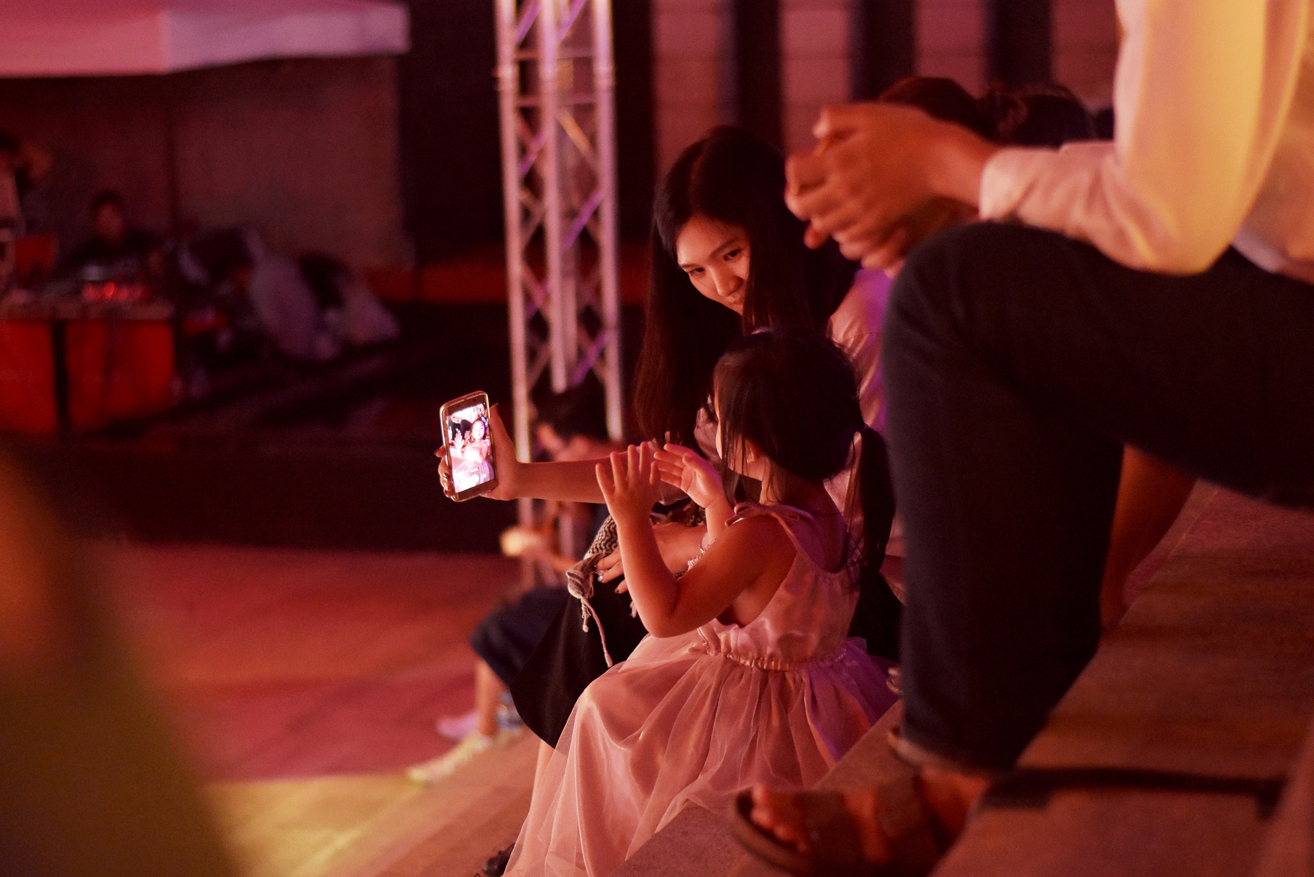 woman holding smartphone and girl sitting wearing white dress photo